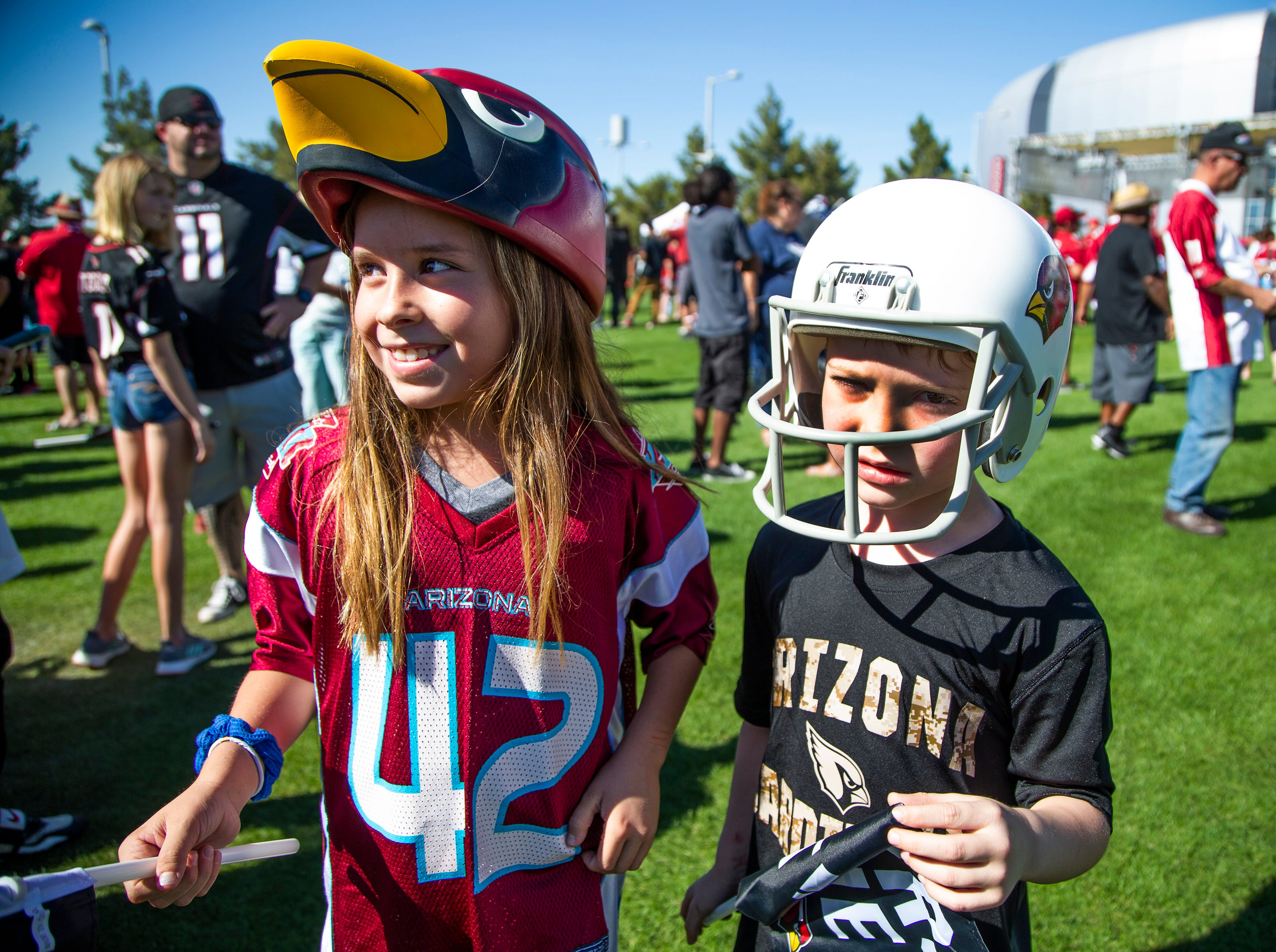 Katelynn Nevarez, 10, left, and her brother, Austin, 6, wear their team hats the Arizona Cardinals NFL Draft party on the Great Lawn outside State Farm Stadium, Thursday, April 25, 2019.