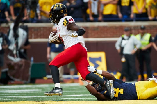 Maryland defensive back Darnell Savage Jr. breaks a tackle by Michigan receiver Nico Collins after intercepting a pass during a game at Michigan Stadium.