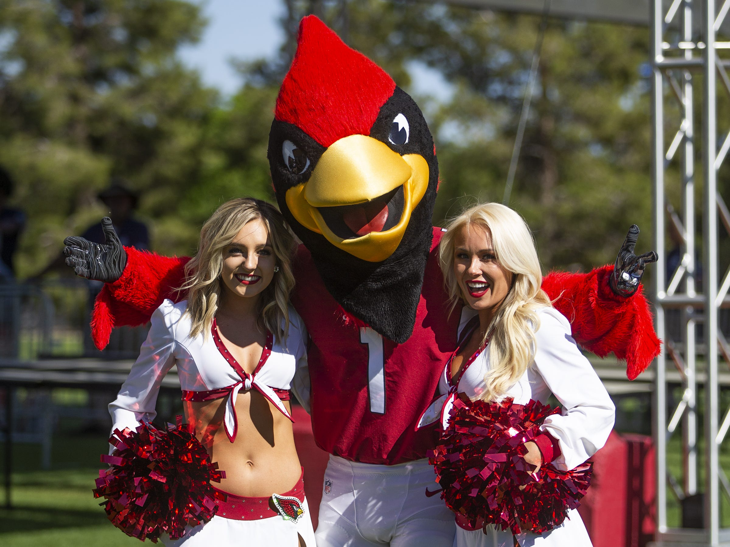 Arizona Cardinals mascot Big Red and Cardinals cheerleaders Shelby, left, and Davis, right, prepare for the crowds to arrive at the NFL Draft party on the Great Lawn outside State Farm Stadium, Thursday, April 25, 2019.