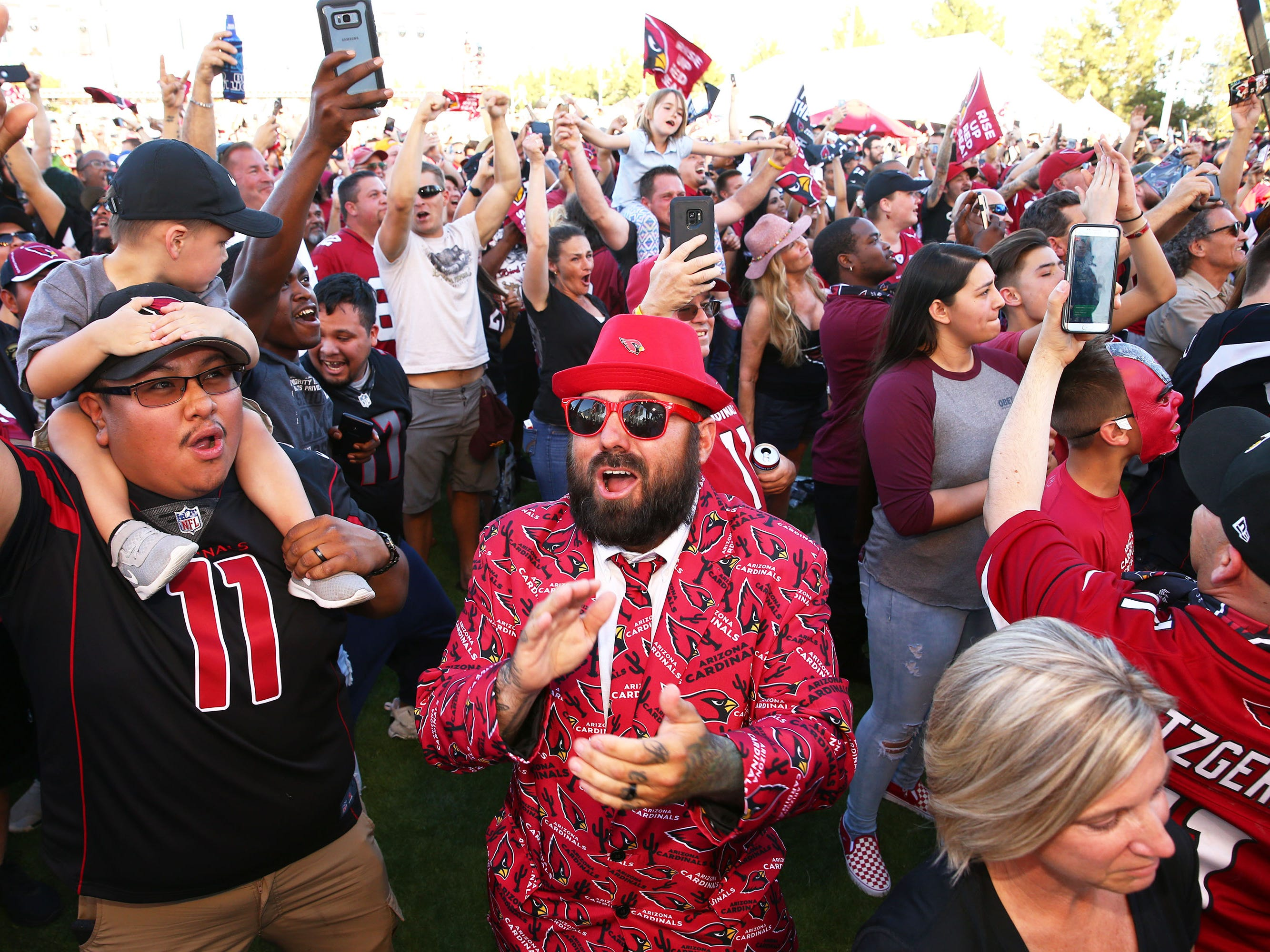 Garret Casados (center) of Surprise, Ariz., reacts after the Arizona Cardinals used their number one draft pick to select quarterback Kyler Murray from Oklahoma during the NFL Draft watch party at State Farm Stadium on Apr. 25, 2019 in Glendale, Ariz.