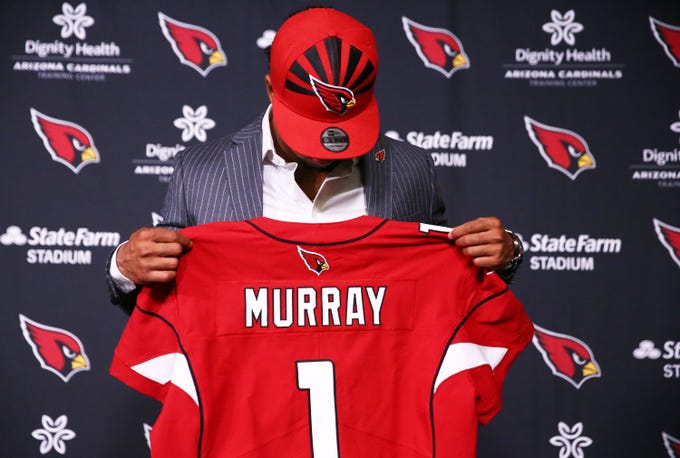 60e213116ed Cardinals first-round draft pick quarterback Kyler Murray looks at his  jersey during an introductory