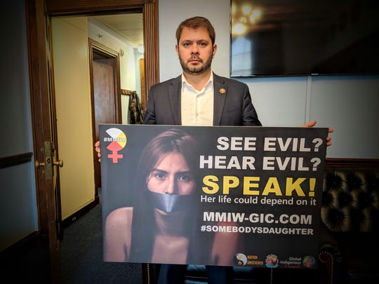 Rep. Ruben Gallego, who represented Arizona's 7th district, holding a scale sized display of the billboards image.