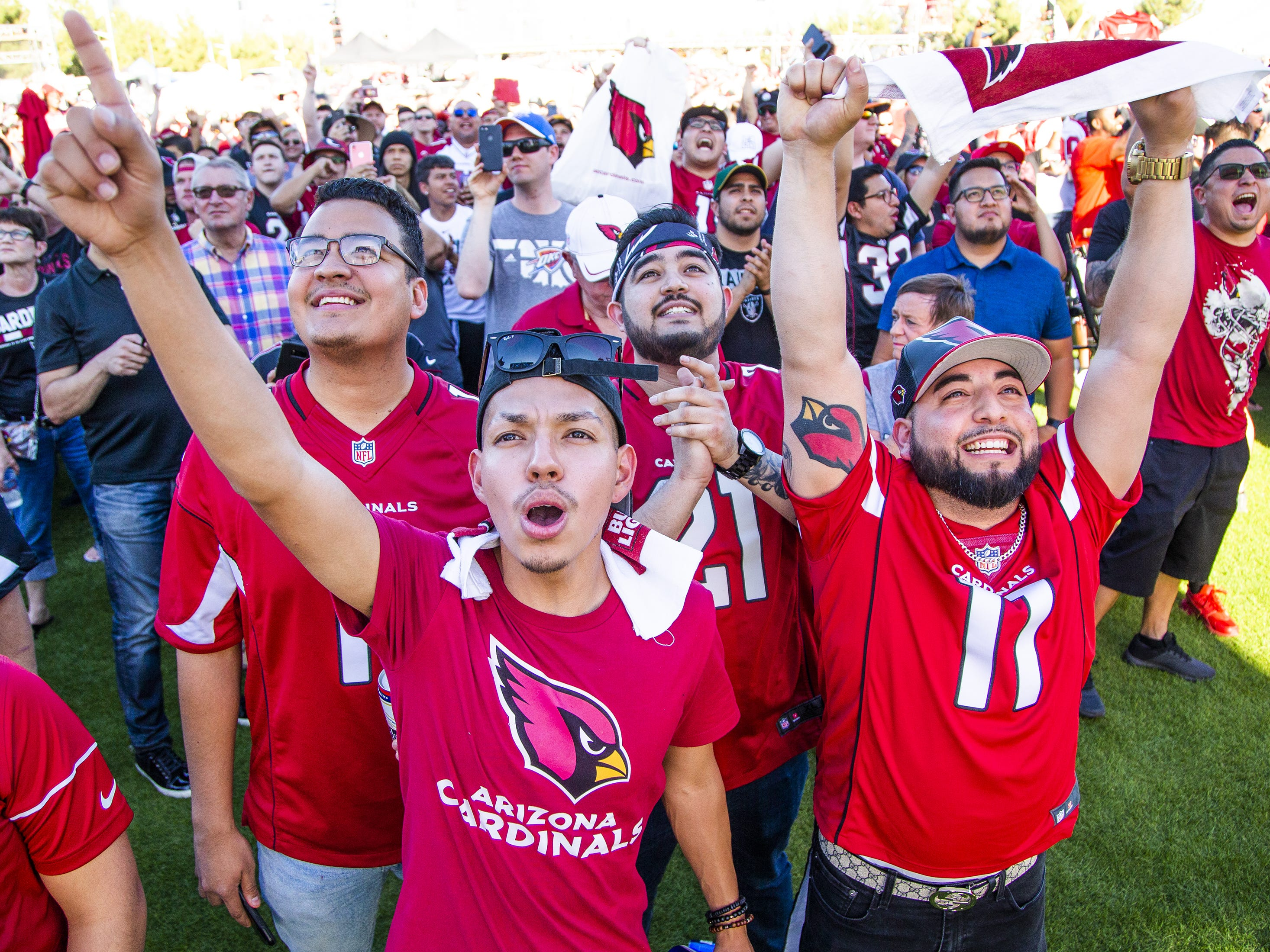 Efren Hernandez, left, Javier Salas, Jesus Cano, and Jesus Quezada, cheer as the Arizona Cardinals make their first pick in the NFL Draft. The fans watched a live feed during a draft party on the Great Lawn outside State Farm Stadium, Thursday, April 25, 2019.