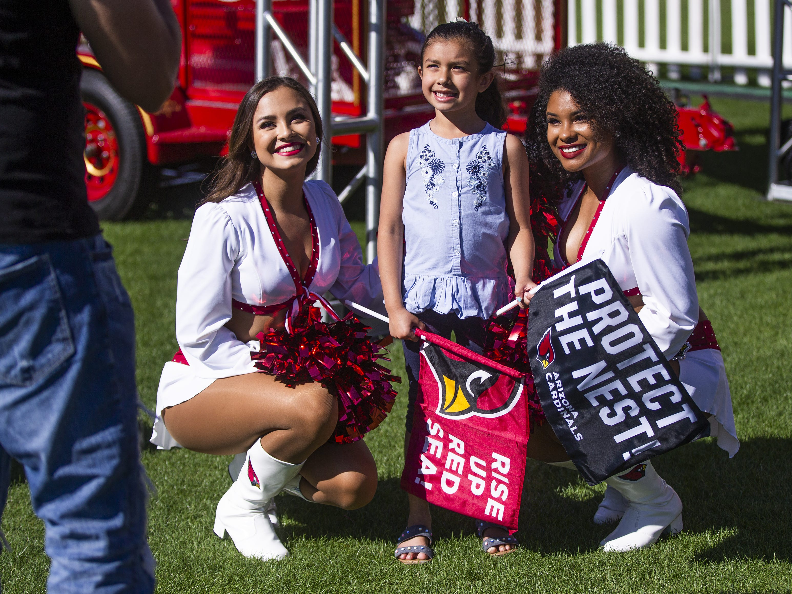 Arizona Cardinals cheerleaders Mandy, left, and Tequasia, right, pose as Basilio Gonzales takes a photo of his daughter, Madison, 5, at the NFL Draft party on the Great Lawn outside State Farm Stadium, Thursday, April 25, 2019.