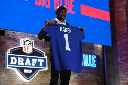 Deandre Baker holds up a New York Giants jersey after being selected in the first round.