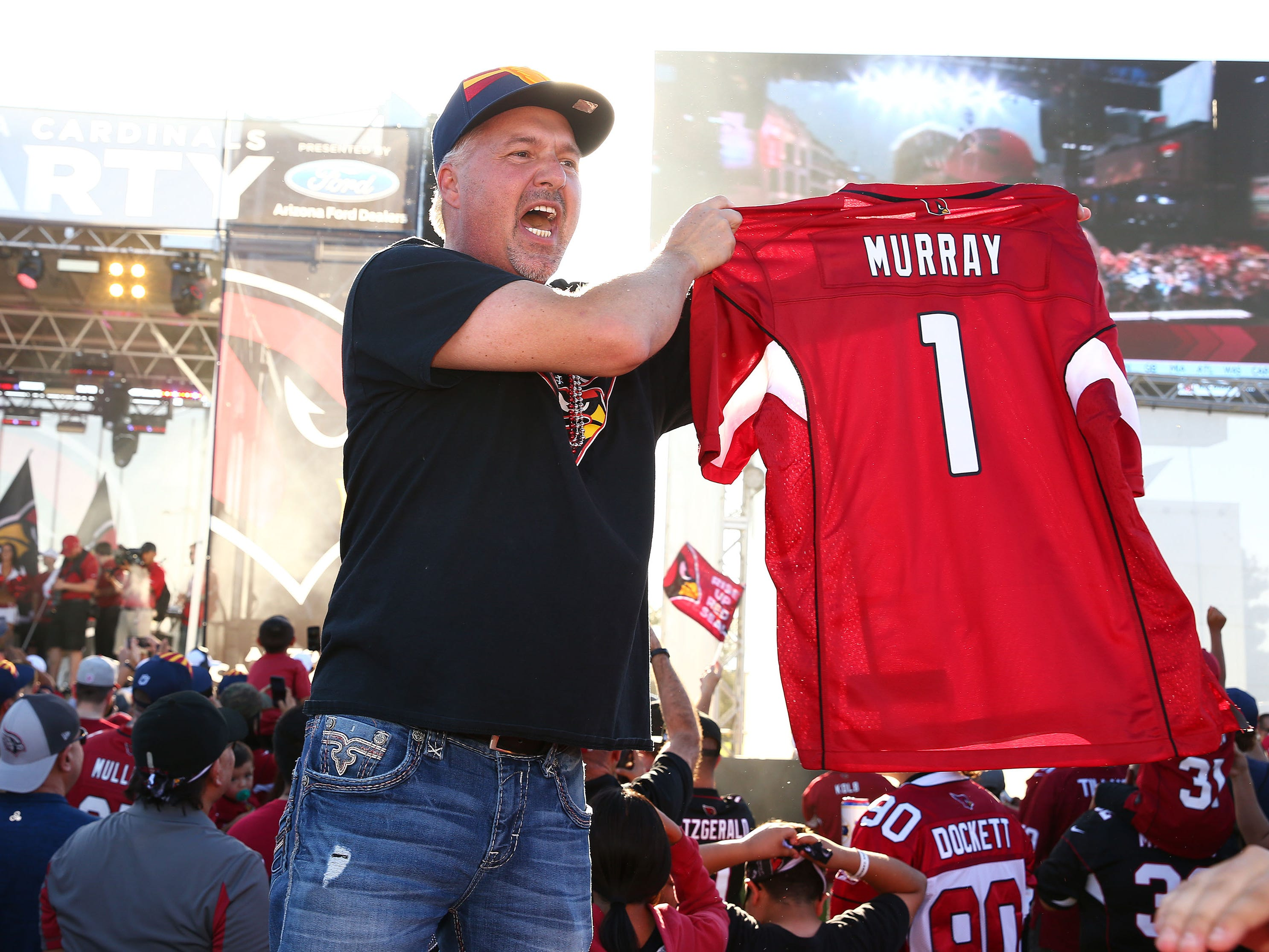 Eric Polansky of Cave Creek, Ariz.,holds-up a Murray jersey after the Arizona Cardinals used their number one draft pick to select quarterback Kyler Murray from Oklahoma during the NFL Draft watch party at State Farm Stadium on Apr. 25, 2019 in Glendale, Ariz.