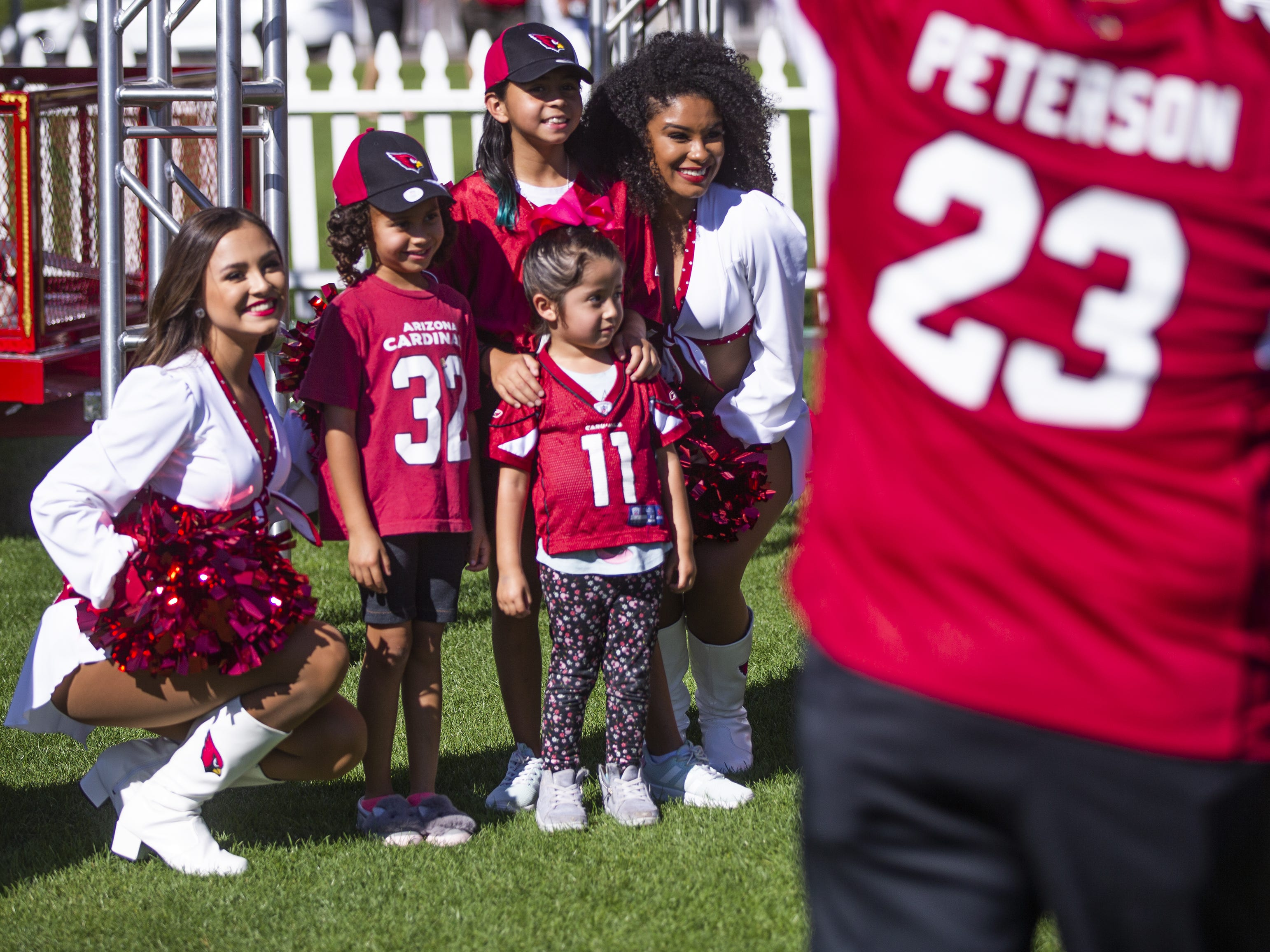 Arizona Cardinals cheerleaders Mandy, left, and Tequasia, right, pose with fans at the NFL Draft party on the Great Lawn outside State Farm Stadium, Thursday, April 25, 2019.