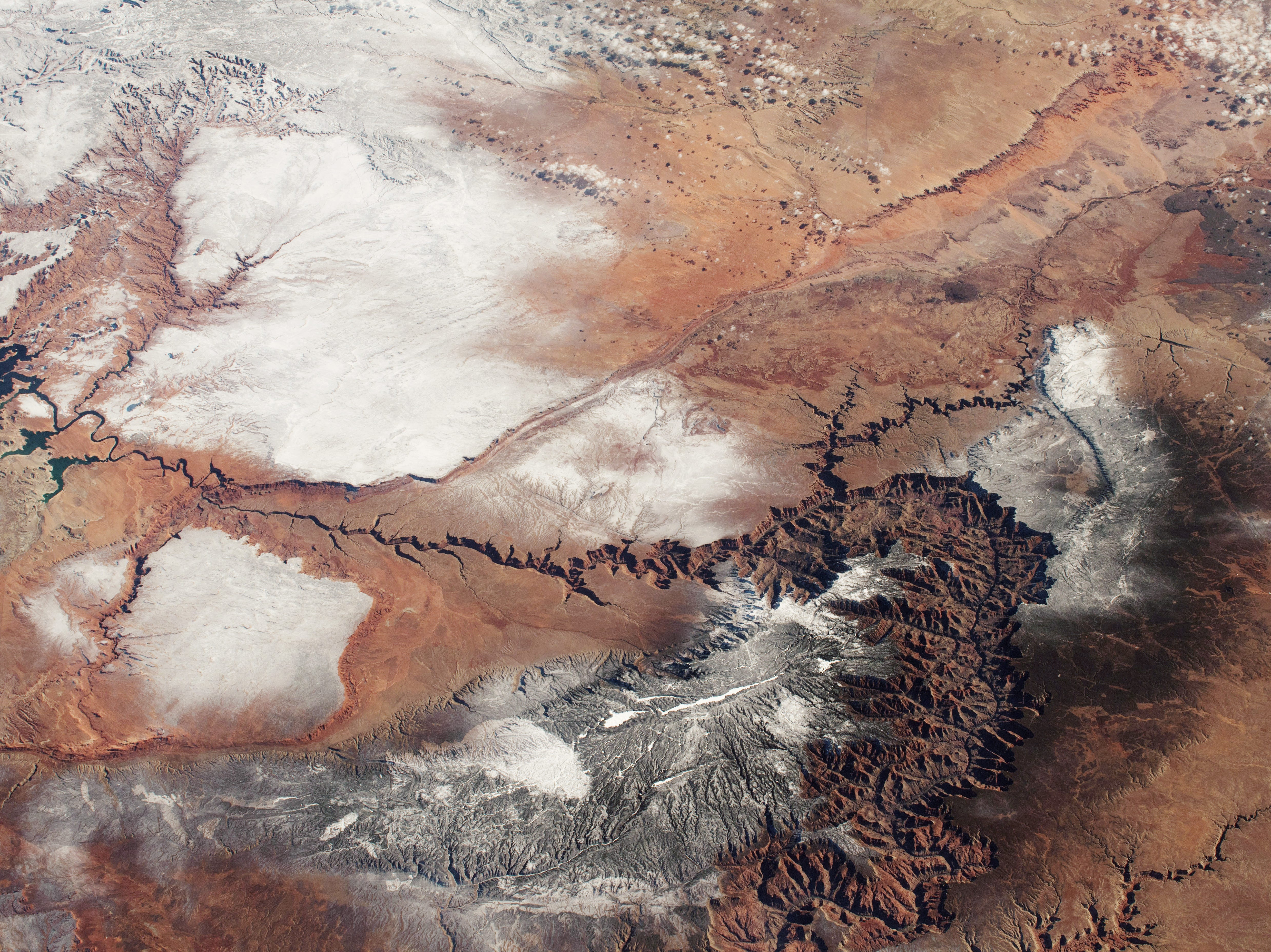 An astronaut aboard the International Space Station focused a camera on the Grand Canyon and surrounding snowy landscapes in northern Arizona on Dec. 29, 2018.  The photograph shows the ragged, steep-sided canyon walls and its numerous side canyons that contrast with the flat surrounding plains. This image was taken from an orbital vantage point over Las Vegas, nearly 240 miles to the west.