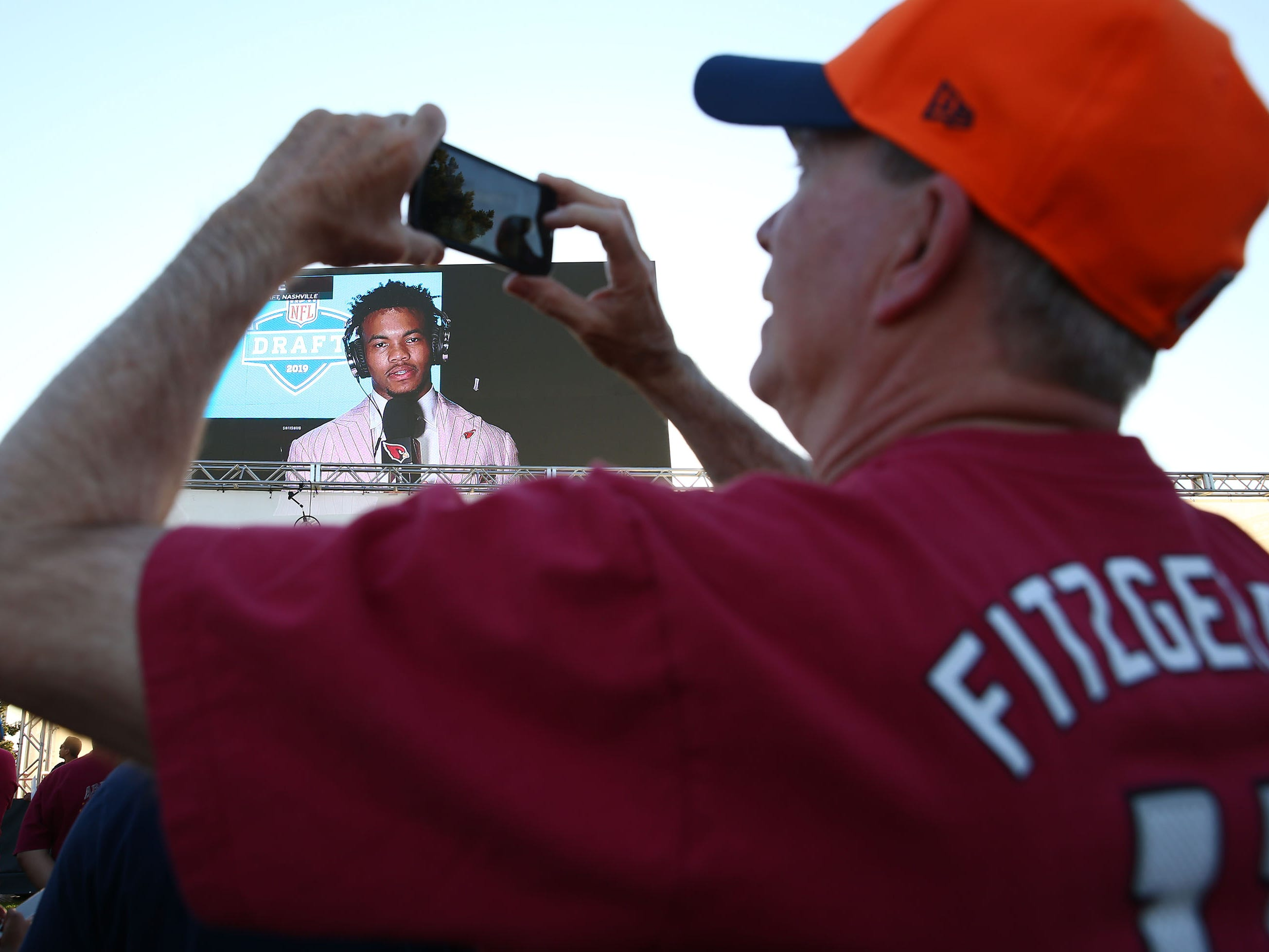 Larry Payton of Glendale, Ariz., takes a picture as the Arizona Cardinals number one draft pick quarterback Kyler Murray from Oklahoma talks to the fans on the Great lawn during the NFL Draft watch party at State Farm Stadium on Apr. 25, 2019 in Glendale, Ariz.