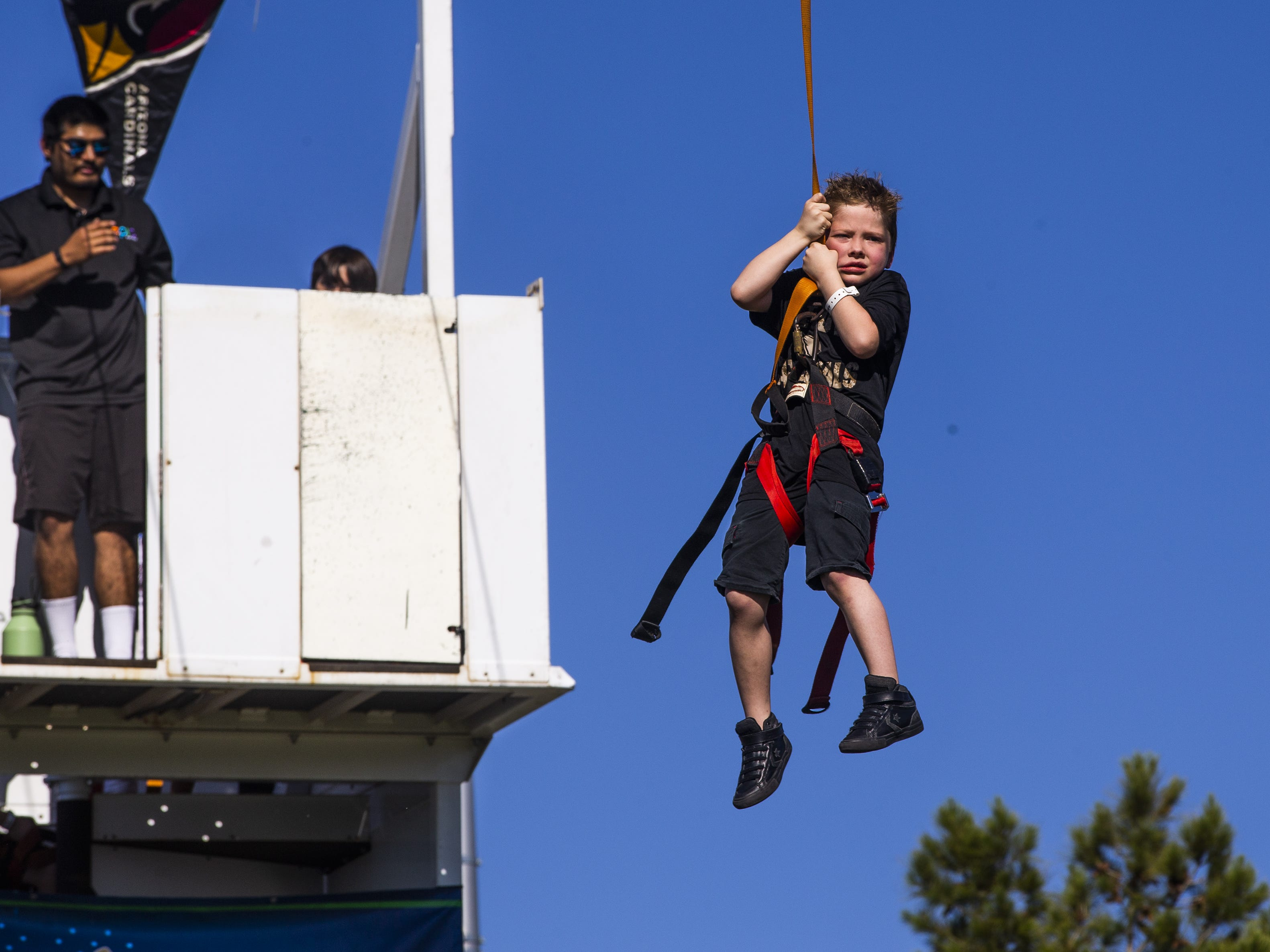 Austin Nevarez, 10, Glendale, slides down the zipline at the NFL Draft party on the Great Lawn outside State Farm Stadium, Thursday, April 25, 2019.