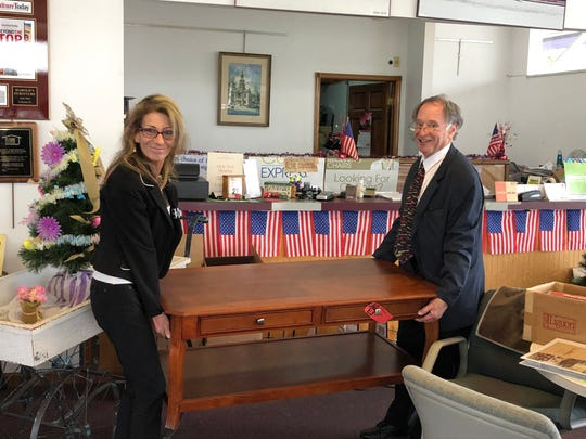 Heather Rocker (left) and Stuart Perlmutter, president of Harold's Furniture, carry a table out to a customer's vehicle.