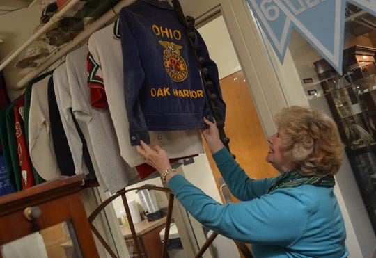 Kathy Steinmiller co-owns the Rocket Shop in Oak Harbor and The End Zone in Port Clinton, where, among other products, the businesss creates varsity jackets. Here, Steinmiller looks at a vintage jacket in Oak Harbor Public Library's history room.