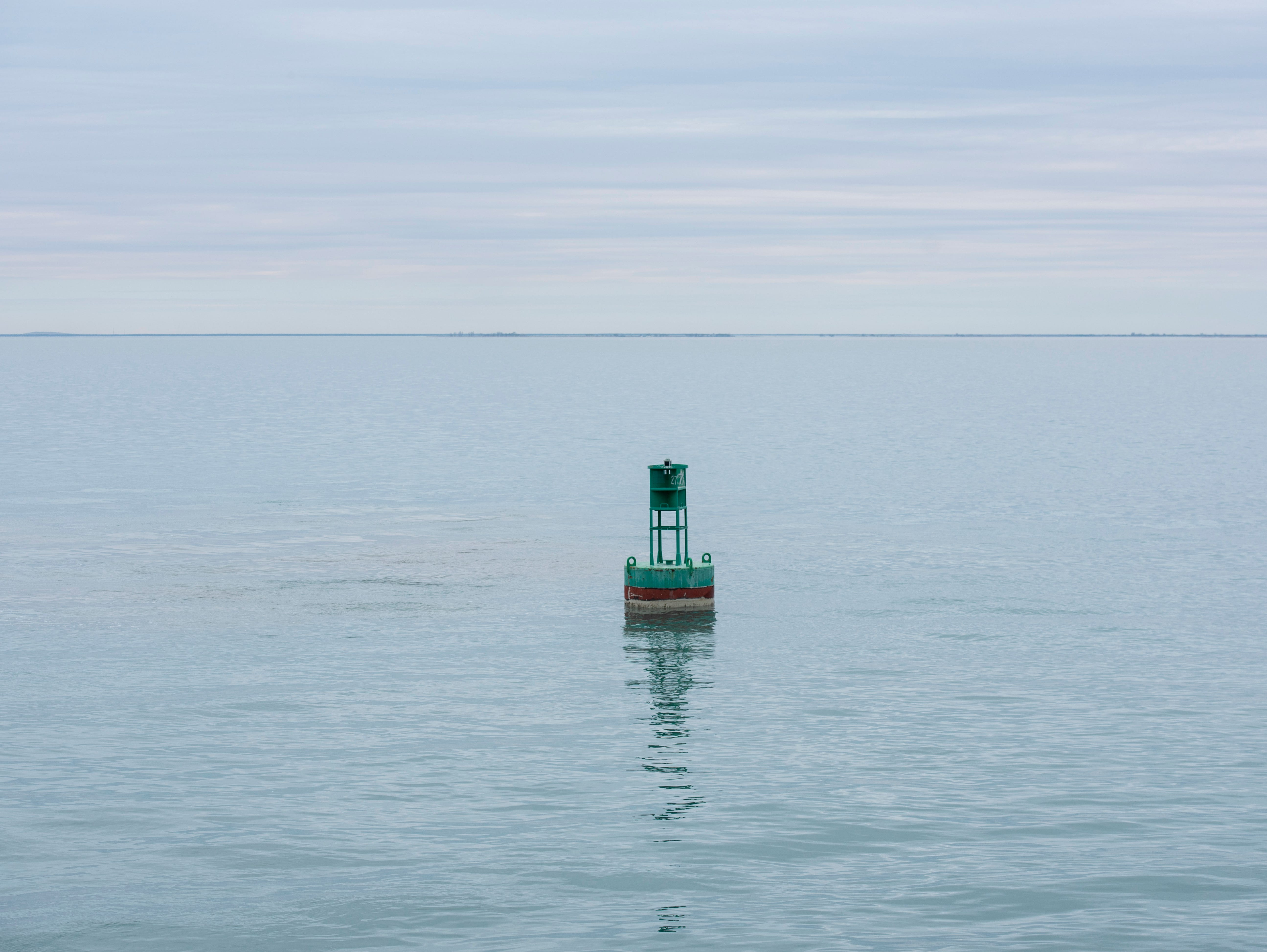 A buoy lowered into Lake St. Clair Thursday, April 25, 2019 by the crew of the USCGC Hollyhock floats on the surface of the lake.