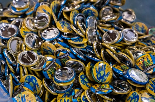 Different varieties of Earth Fair buttons are handed out during the event this weekend at Goodells County Park.