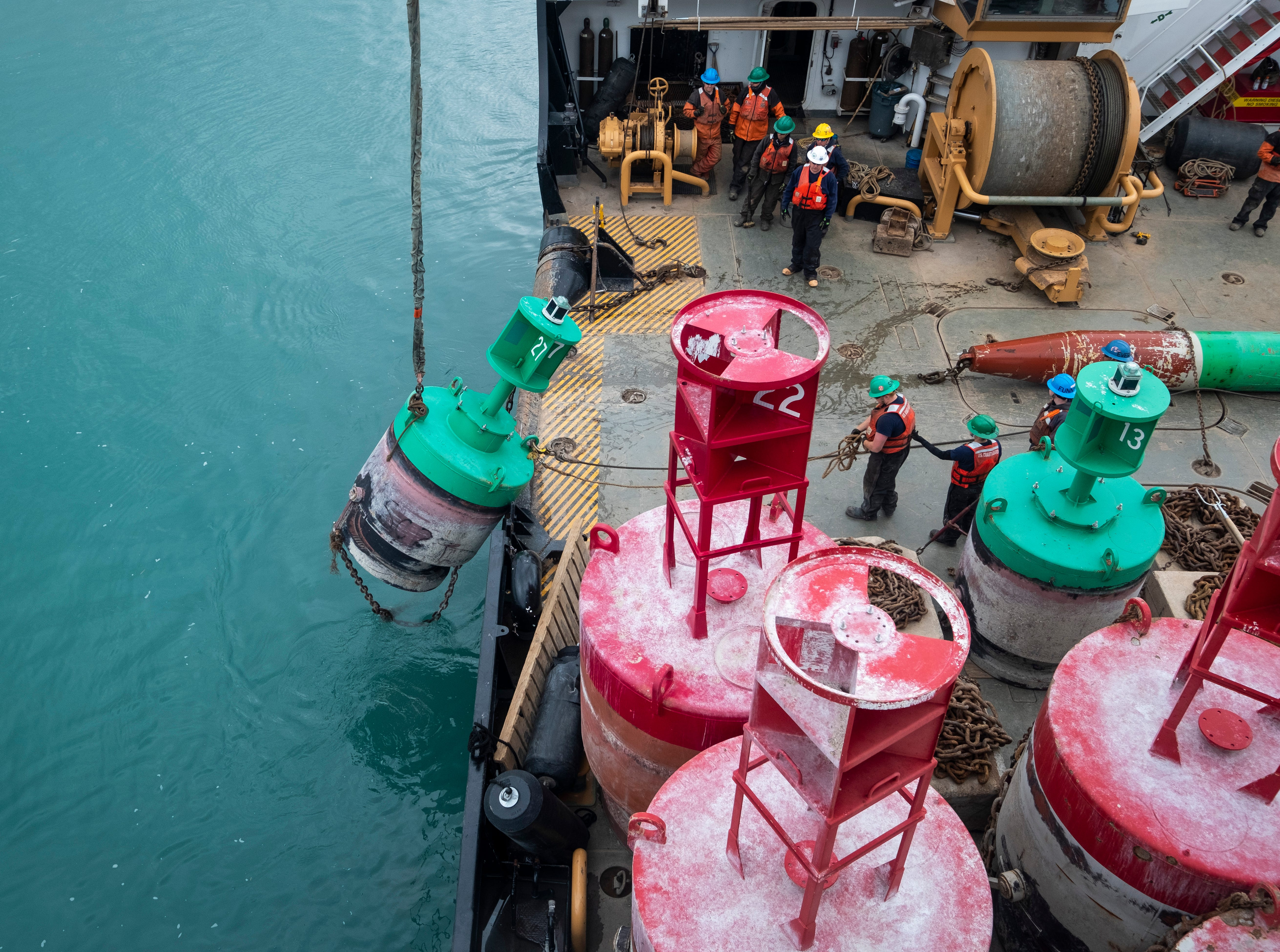 After the first winter buoy of the day has been removed from the water, crews work to set a summer buoy into the river in its place Thursday morning, April 25, 2019. Winter buoys are designed to be able to ride under the ice and handle the pressure of ice pressing against its hull, while summer buoys are illuminated and easier to spot. Each buoy is attached to a stone of varying weight that sits on the bottom of the waterway.