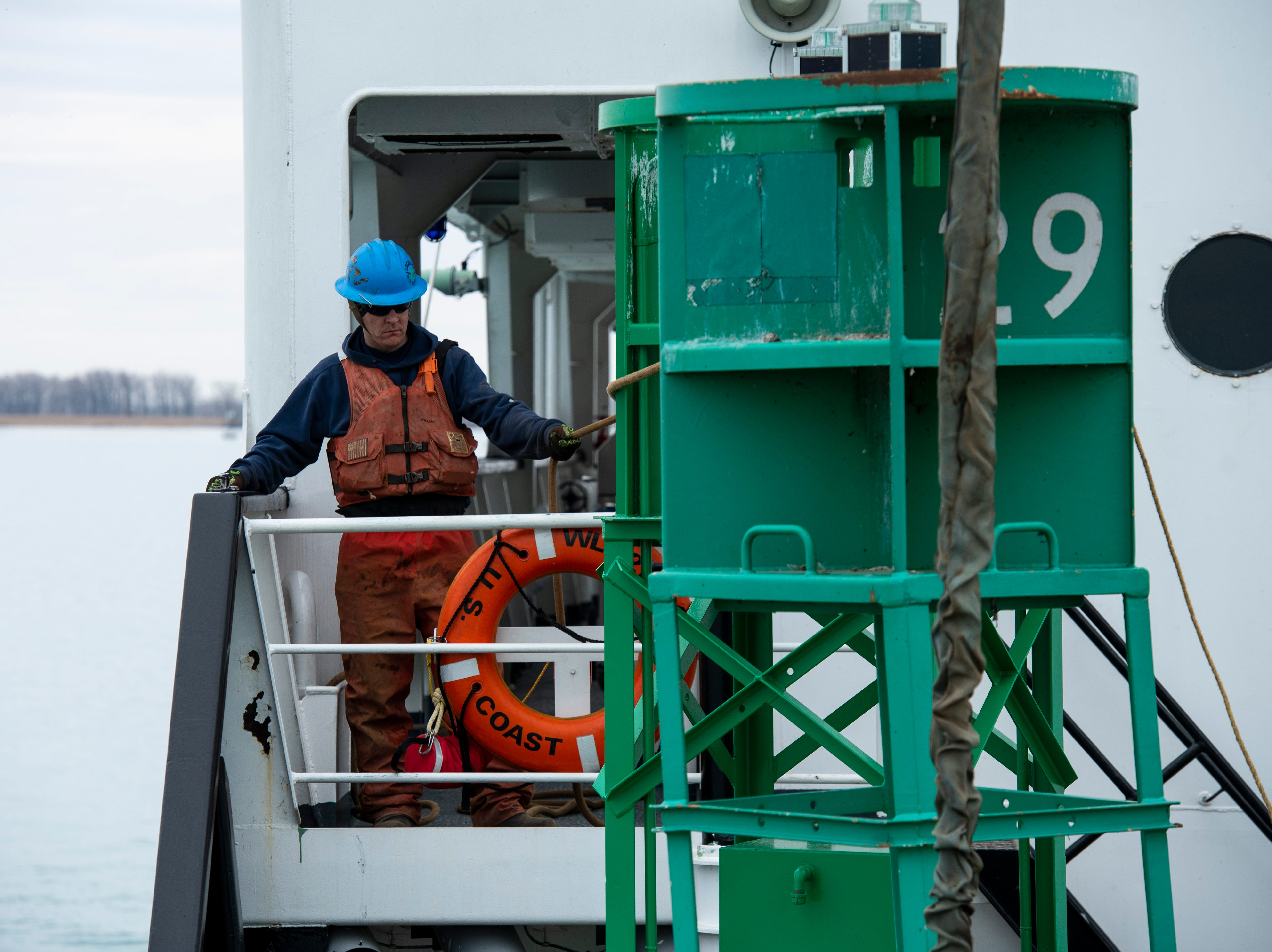 U.S. Coast Guard SK2 Tanner Bartholomew holds a line on a buoy Thursday, April 25, 2019 aboard the USCGC Hollyhock on Lake St. Clair. As each buoy is set into the water, a minimum of two lines are attached to the buoy. The opposing force of the lines helps to keep the buoy from spinning too far while also keeping it close to the ship once in the water.
