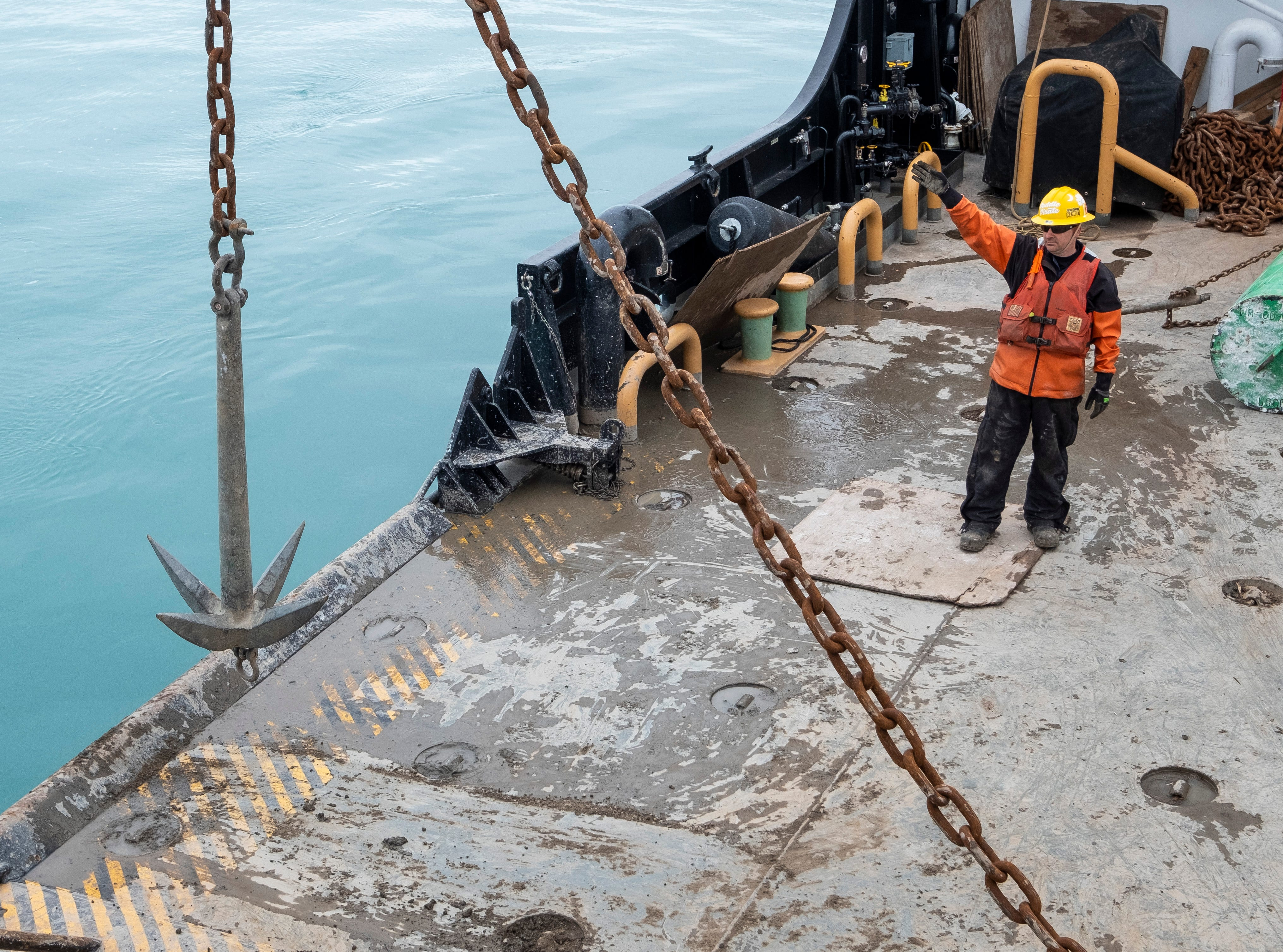 U.S. Coast Guard BMC Jeffrey Rogers motions ot the Hollyhock's crane operator as a grapple is moved over the side of the buoy deck Thursday, April 25, 2019. One of the buoys the crew was scheduled to swap had gone missing over the winter. The grapple would bounce along the bottom of the lake to attempt to find the stone, buoy or chain so it could be removed. If a new buoy was set on top of it, the chains could become twisted or other problems could be caused.