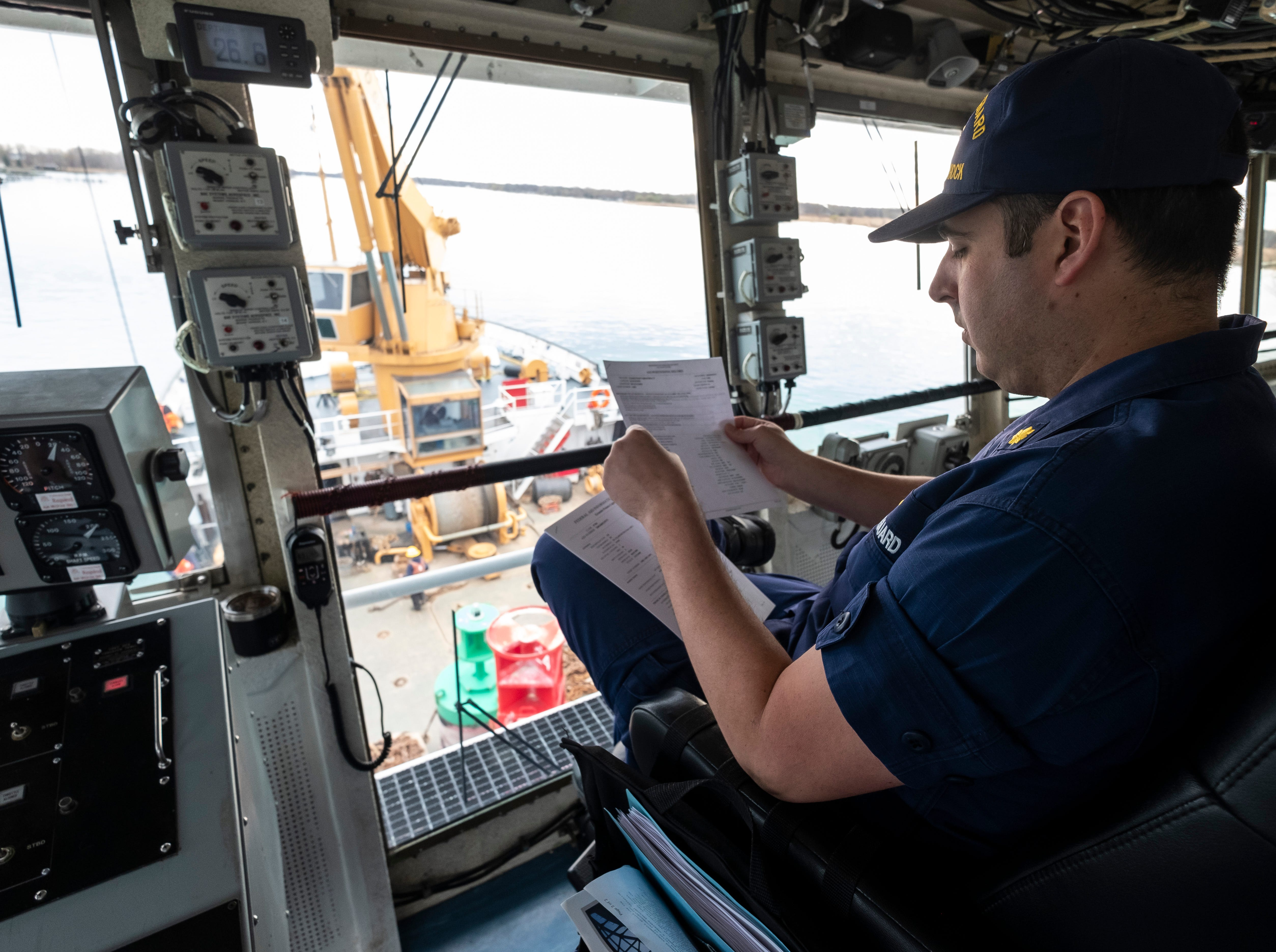 """U.S. Coast Guard Lt. Cmdr. Nick Monacelli, the Hollyhock's captain, looks over the Aid Positioning Record on the ship's bridge Thursday morning, April 25, 2019. The log shows a history of where each buoy was found and placed and is signed off and certified by the captain. """"It's our due diligence,"""" he said of the report."""