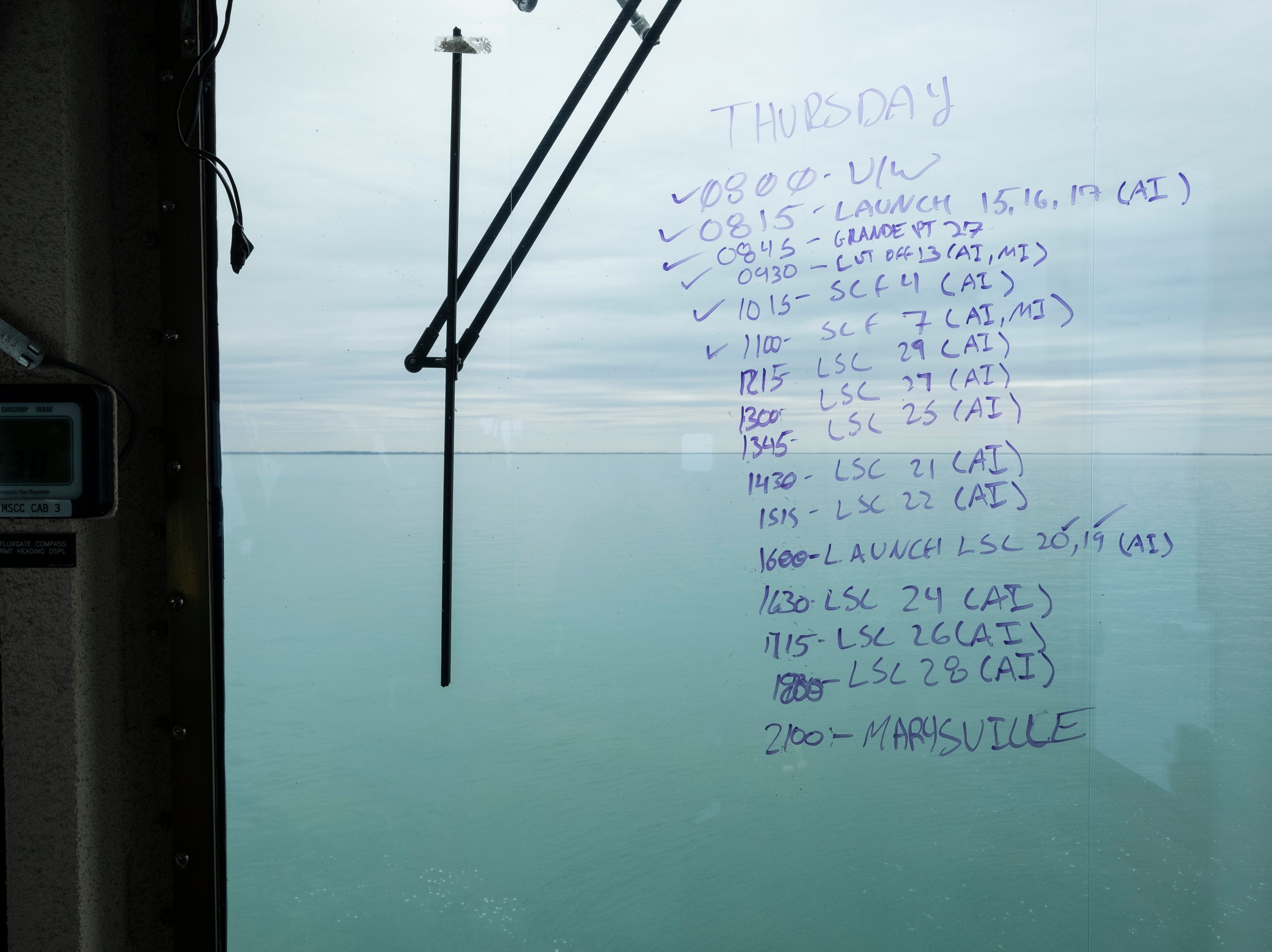 The schedule for the day's operation is written in dry erase marker on a window on the USCGC Hollyhock's bridge.