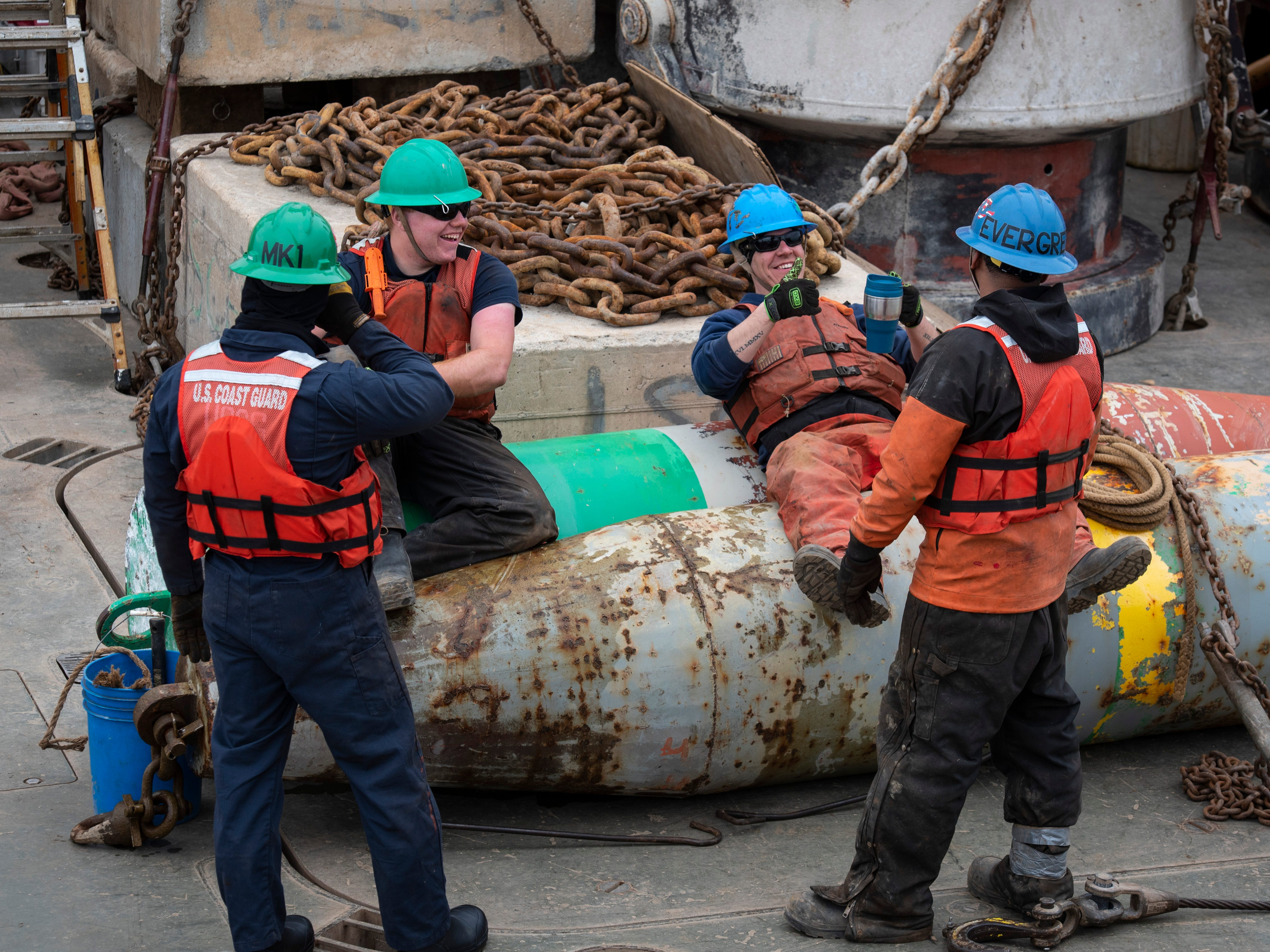 While the USCGC Hollyhock travels to the next buoy, several crewmembers relax on top of winter buoys that have been removed from the water Thursday, April 25, 2019.