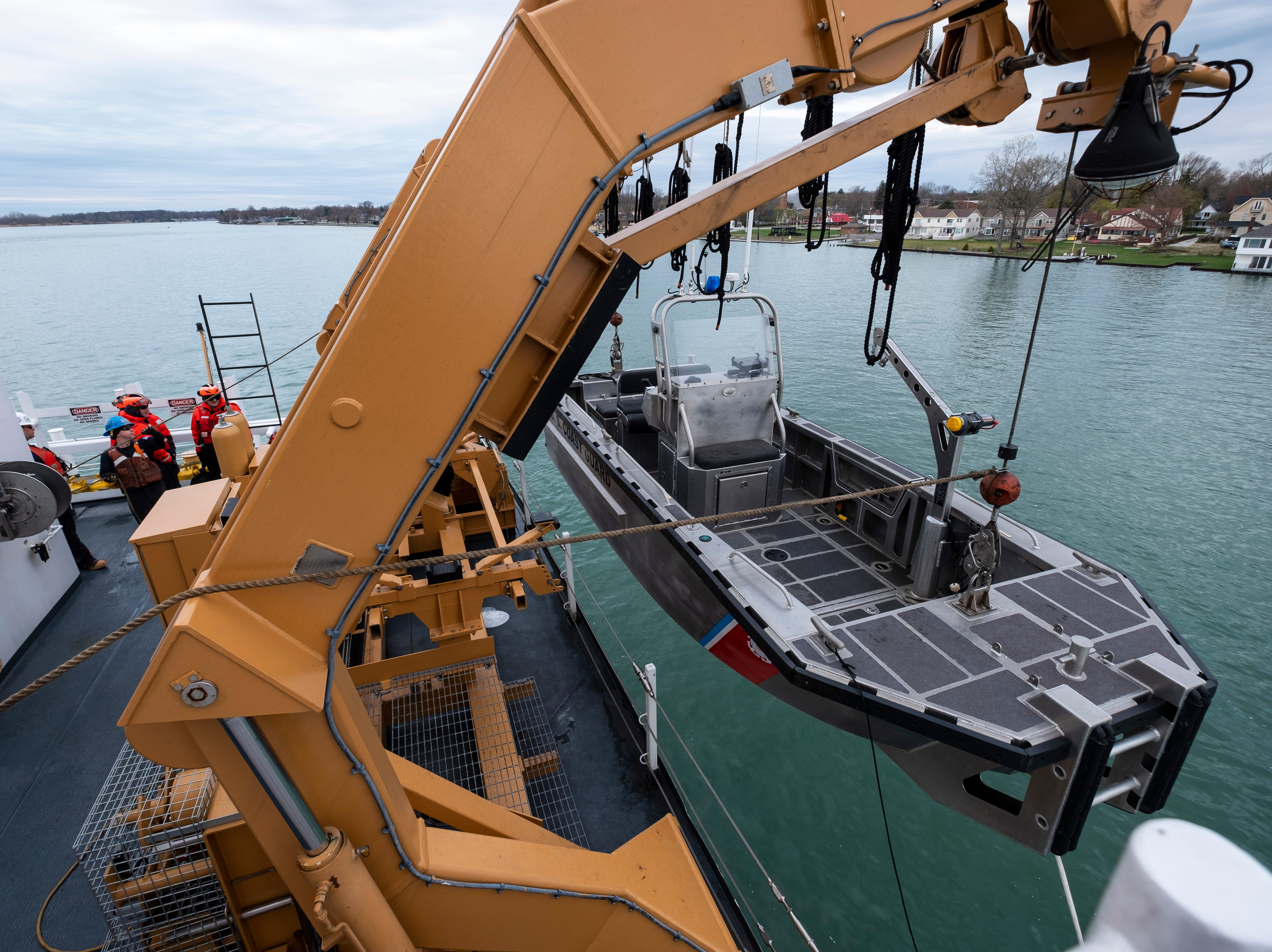 """Crewmembers prepare to lower the Hollyhock's Aids to Navigation System, or ATON boat as the ship pulls away from the Algonac pier Thursday morning, April 25, 2019. The boat is being deployed with several crewmembers to help complete the day's work by doing simpler tasks on buoys that wouldn't need to be removed from the water, such as replacing lights. """"It allows us to do two jobs at once,"""" said U.S. Coast Guard Lt. Cmdr. Nick Monacelli, Hollyhock's captain."""