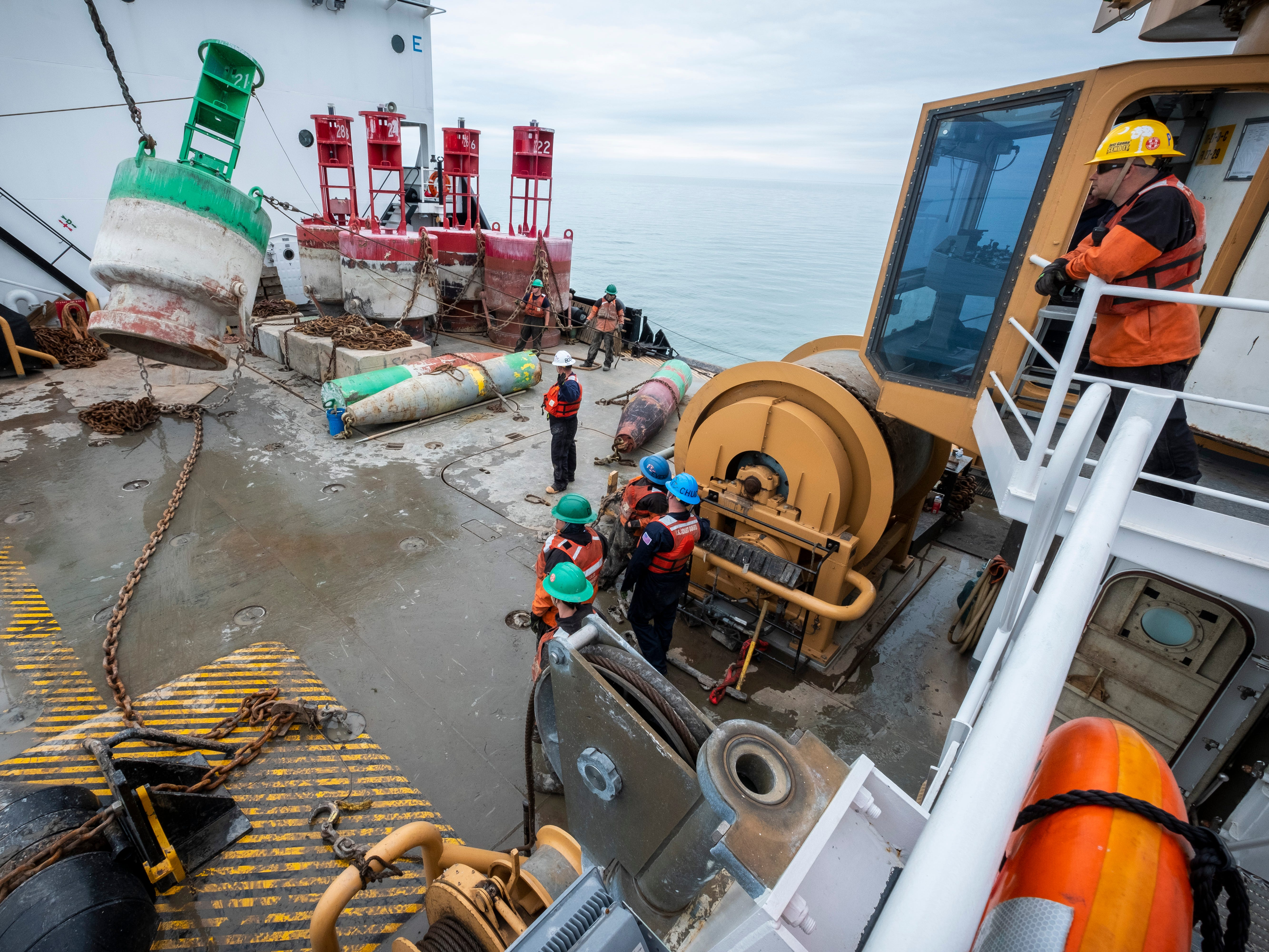 U.S. Coast Guard BMC Jeffrey Rogers, right, watches as crewmembers move a buoy off the deck of the USCGC Hollyhock Thursday, April 25, 2019. From his position on the forward deck, BMC Rogers watches to ensure the crew is operating safely while working with the bridge to obtain permission to move buoys and stones.