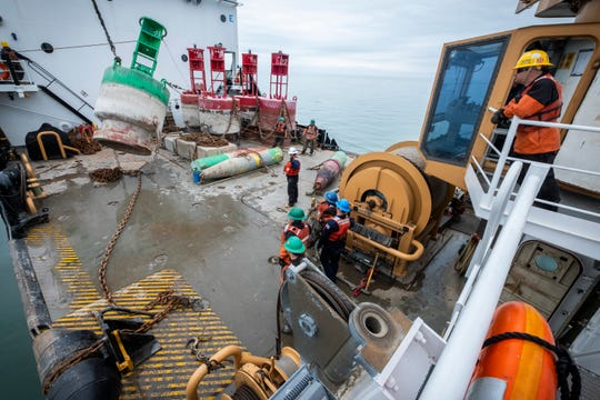 U.S. Coast Guard BMC Jeffrey Rogers, right, watches as crewmembers move a buoy off the deck of the USCGC Hollyhock Thursday, April 25, 2019 on Lake St. Clair. The day's schedule sent the ship and its crew to work 17 buoys, which was more than the ship's previous record of 14 worked in a day.