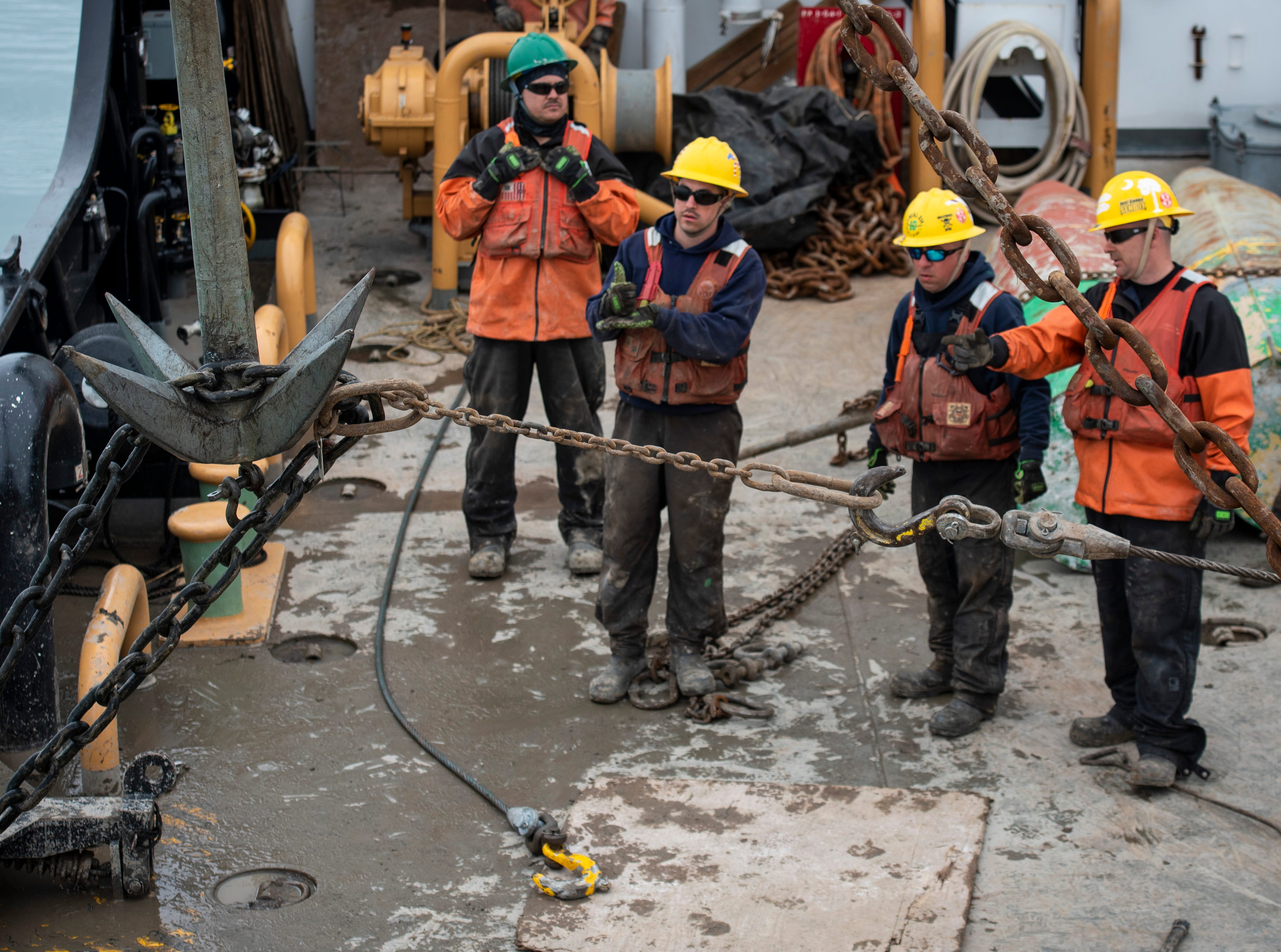 A second line is added to help pull the sunken buoy's chain onto the Hollyhock's deck. Once the chain is secured, it will be cut so the sunken buoy and its stone can be brought up individually.