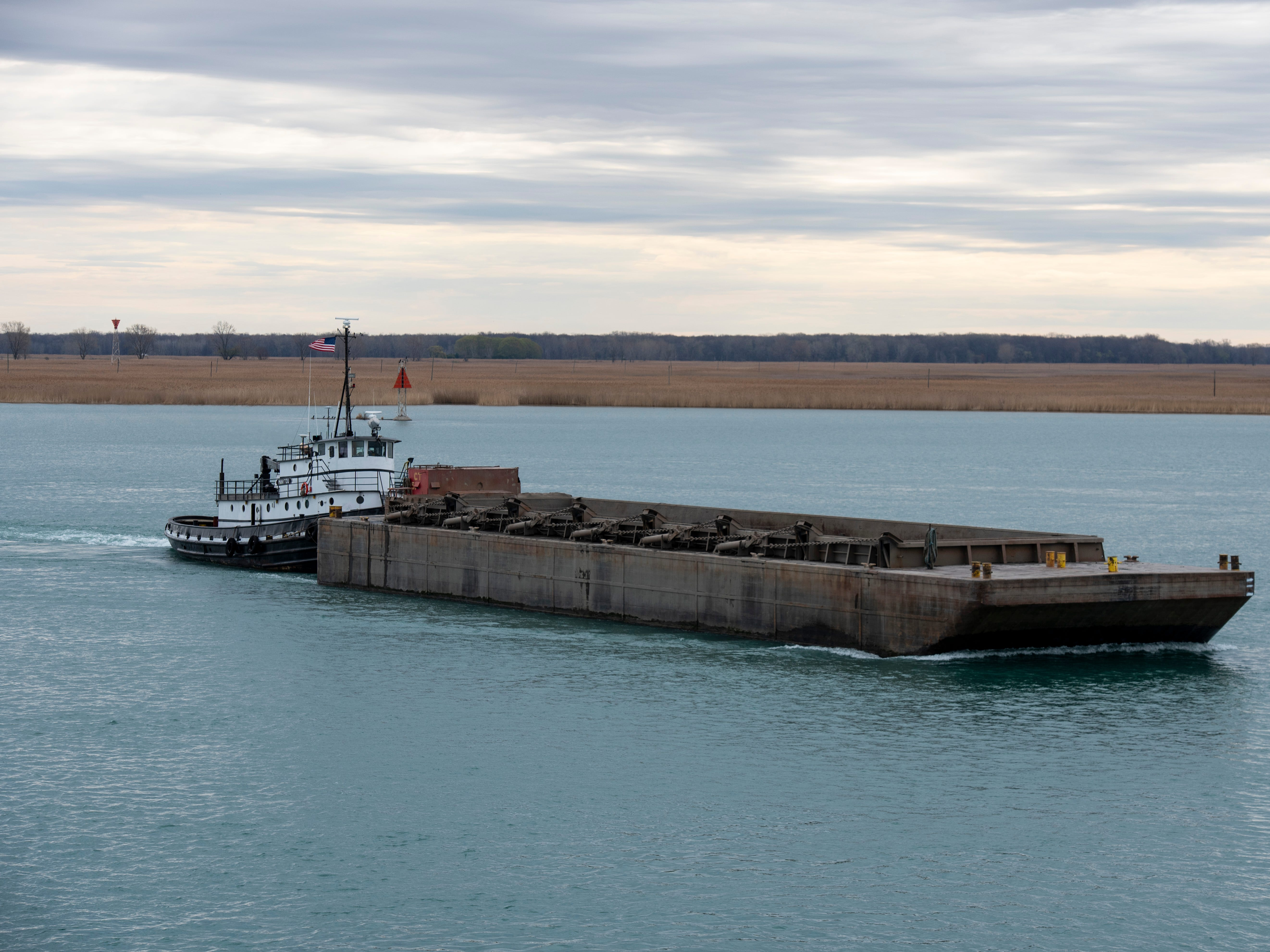 The tug Manitou, owned by Malcolm Marine, Inc., pushes a small barge past the USCGC Hollyhock Thursday morning, April 25, 2019 on the St. Clair River.