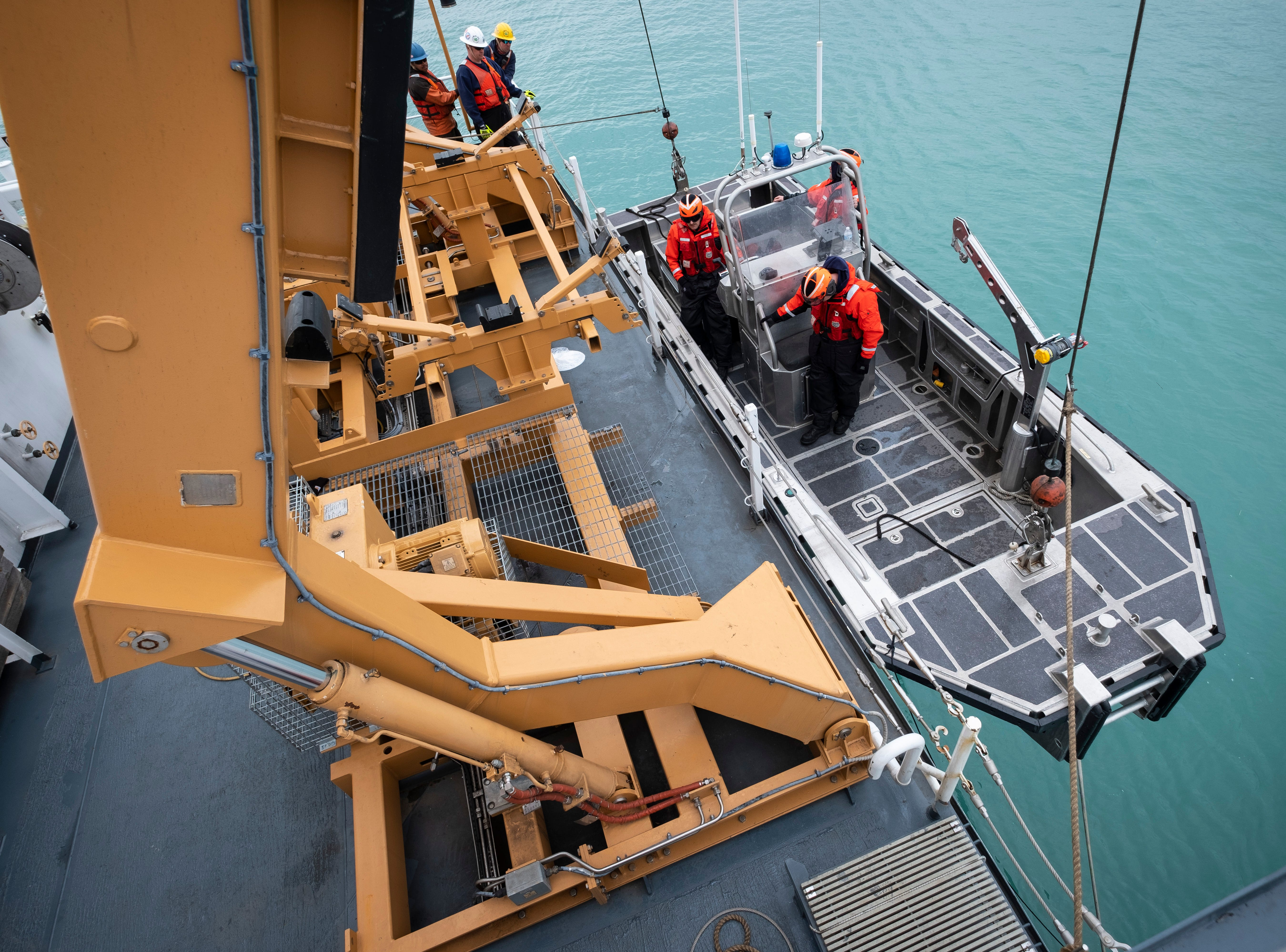After completing their work early Thursday, April 25, 2019, several of the Hollyhock's crewmembers and the ship's ATON boat are lifted back aboard.
