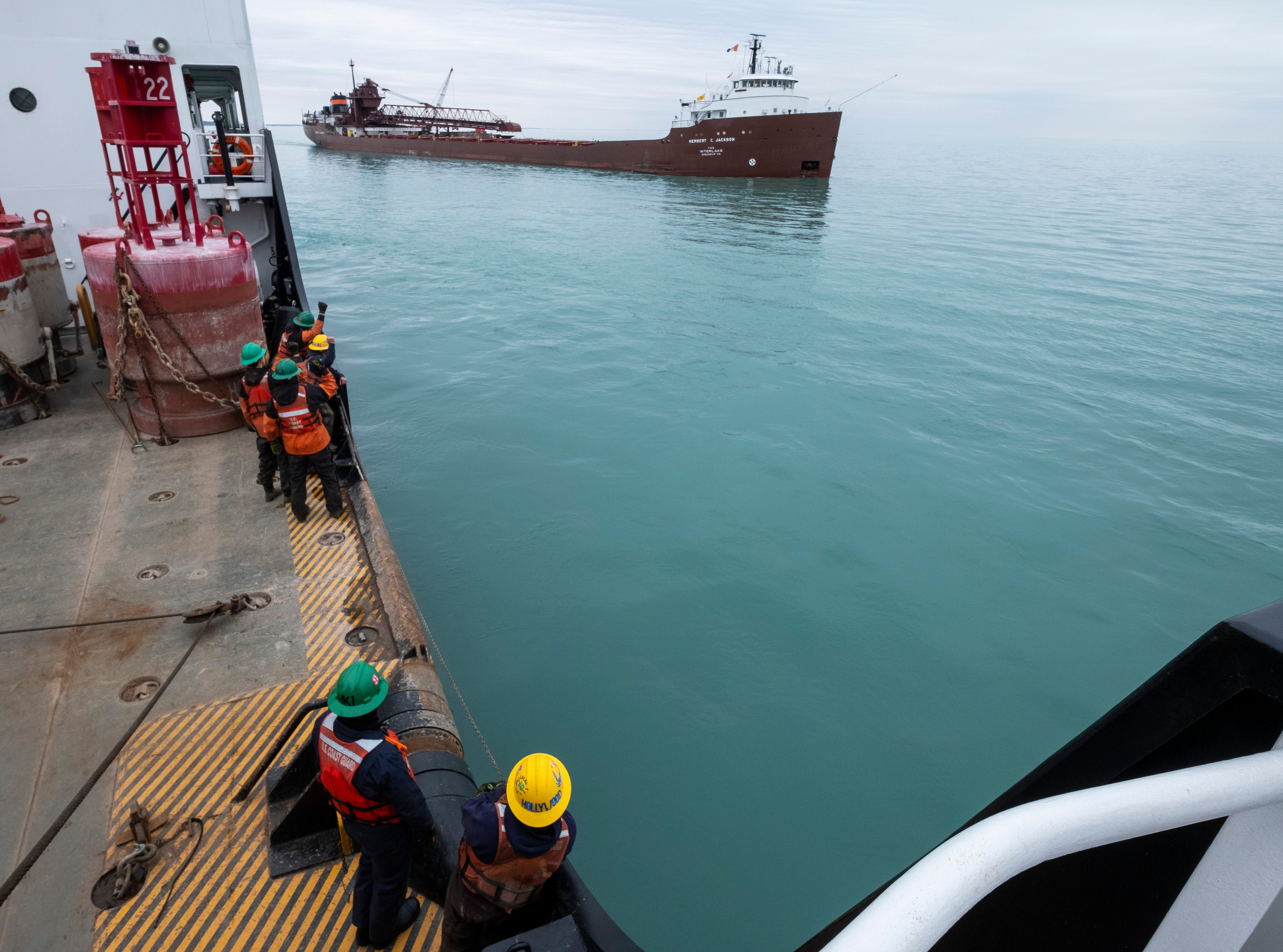 """Crewmembers on the USCGC Hollyhock's buoy deck shout """"toot it!"""" to the passing Herbert C. Jackson freighter while making gestures to the ship's crew to blow its horn Thursday, April 25, 2019 on Lake St. Clair."""