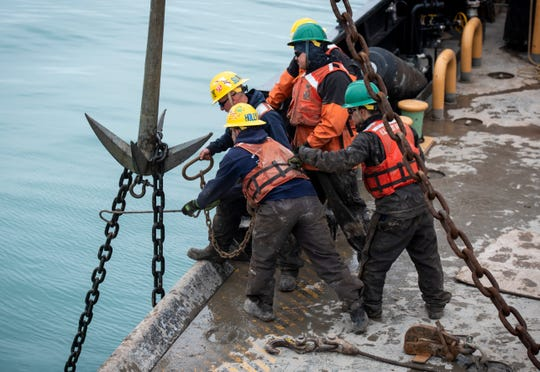 As the chain for the sunken buoy is lifted out of the water, the ship's crane became overloaded. Crewmembers work to secure the chain to the ship so the ship's main crane can be used.