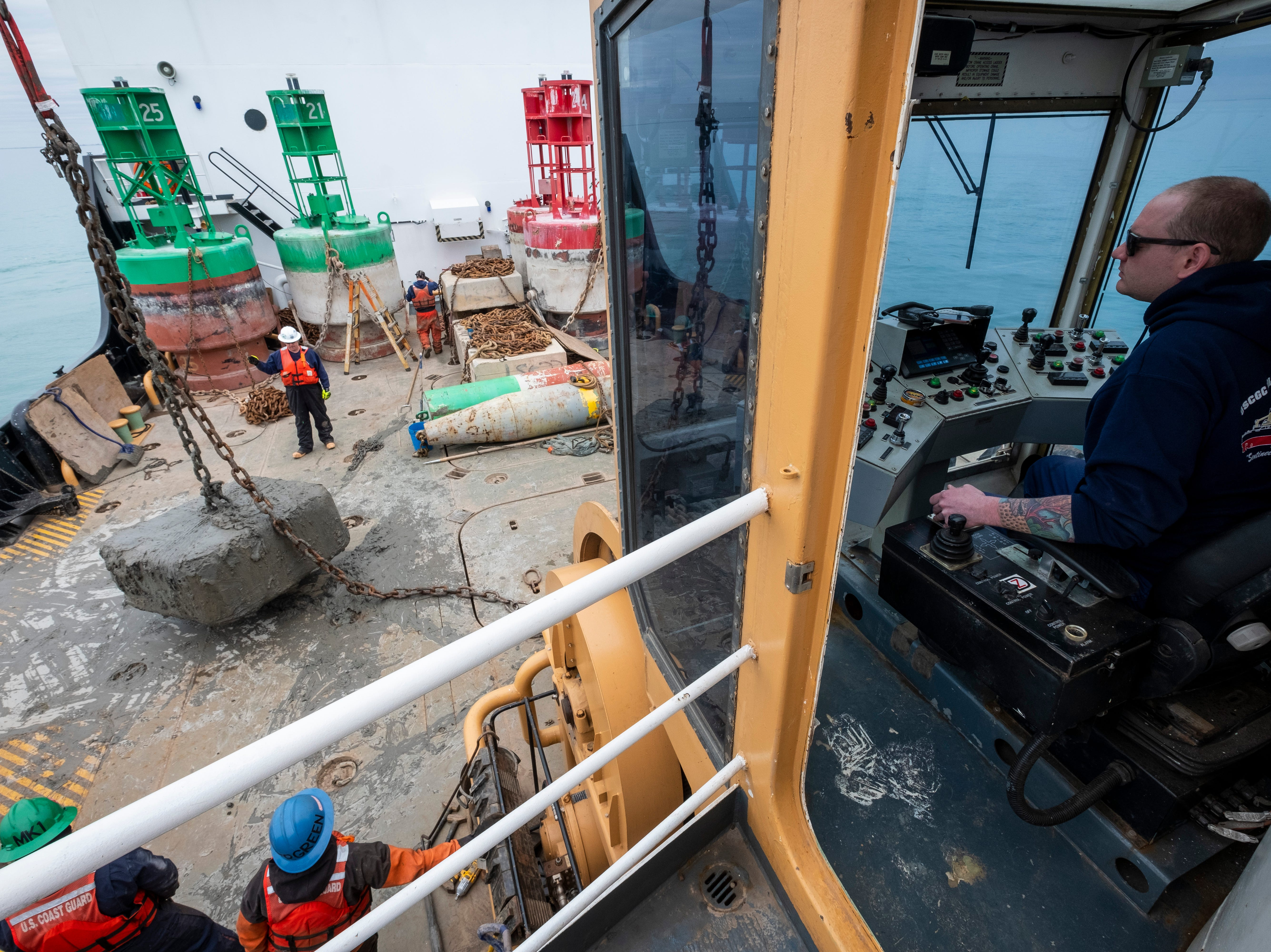 """U.S. Coast Guard HS1 Joshua Simpson operates the Hollyhock's crane to move a large stone back into Lake St. Clair from the ship's deck Thursday, April 25, 2019. Simpson is the ship's primary medical person, but he also enjoys operating the crane. """"I just like to come up here and have fun on here,"""" he said. """"Once I finish my job and it's more relaxed, I'll come up here and hang out."""""""