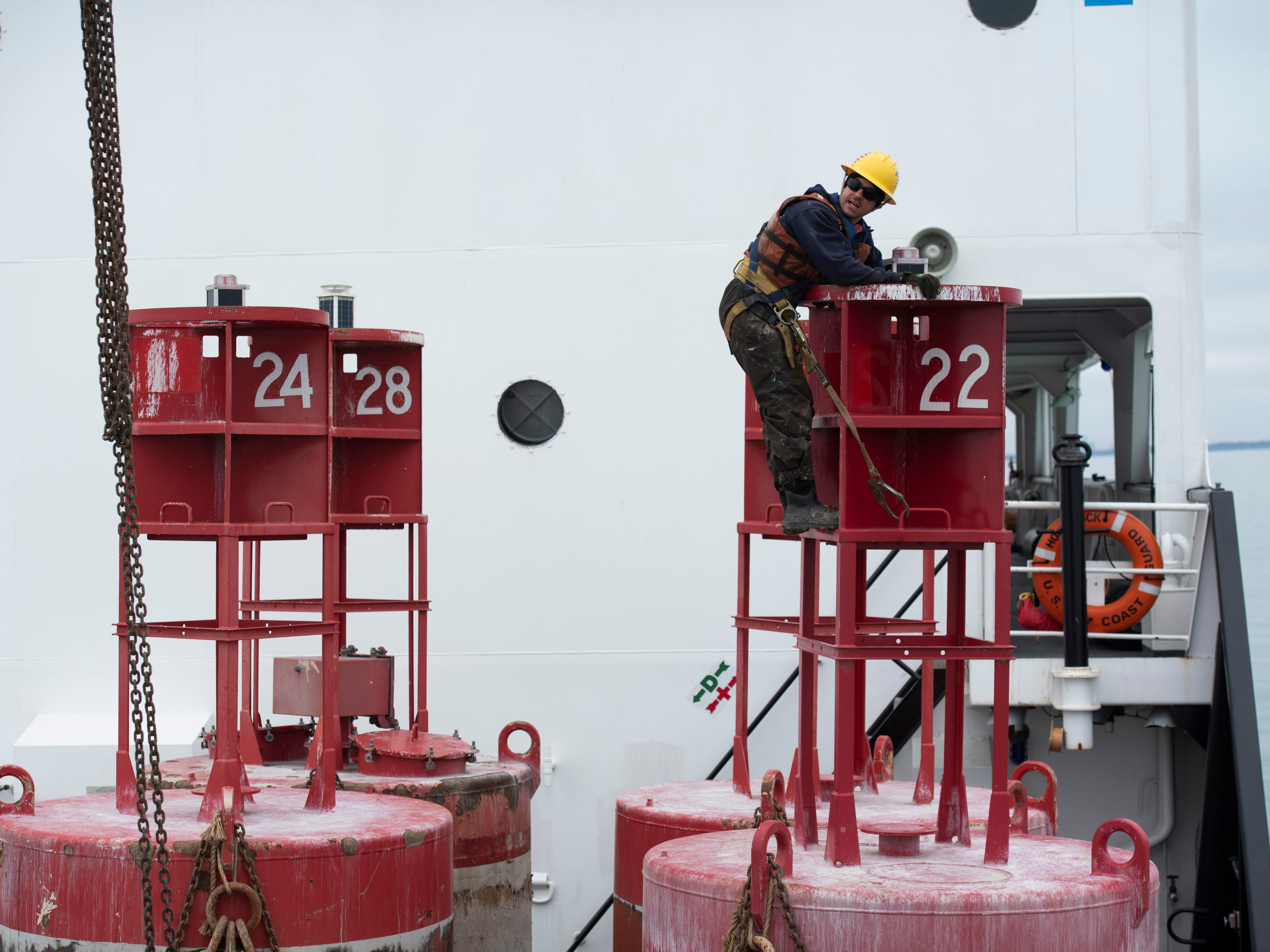 U.S. Coast Guard BM2 Nicholas Cavallarro climbs to the top of a buoy to inspect its light before it is set back into Lake St. Clair Thursday, April 25, 2019.