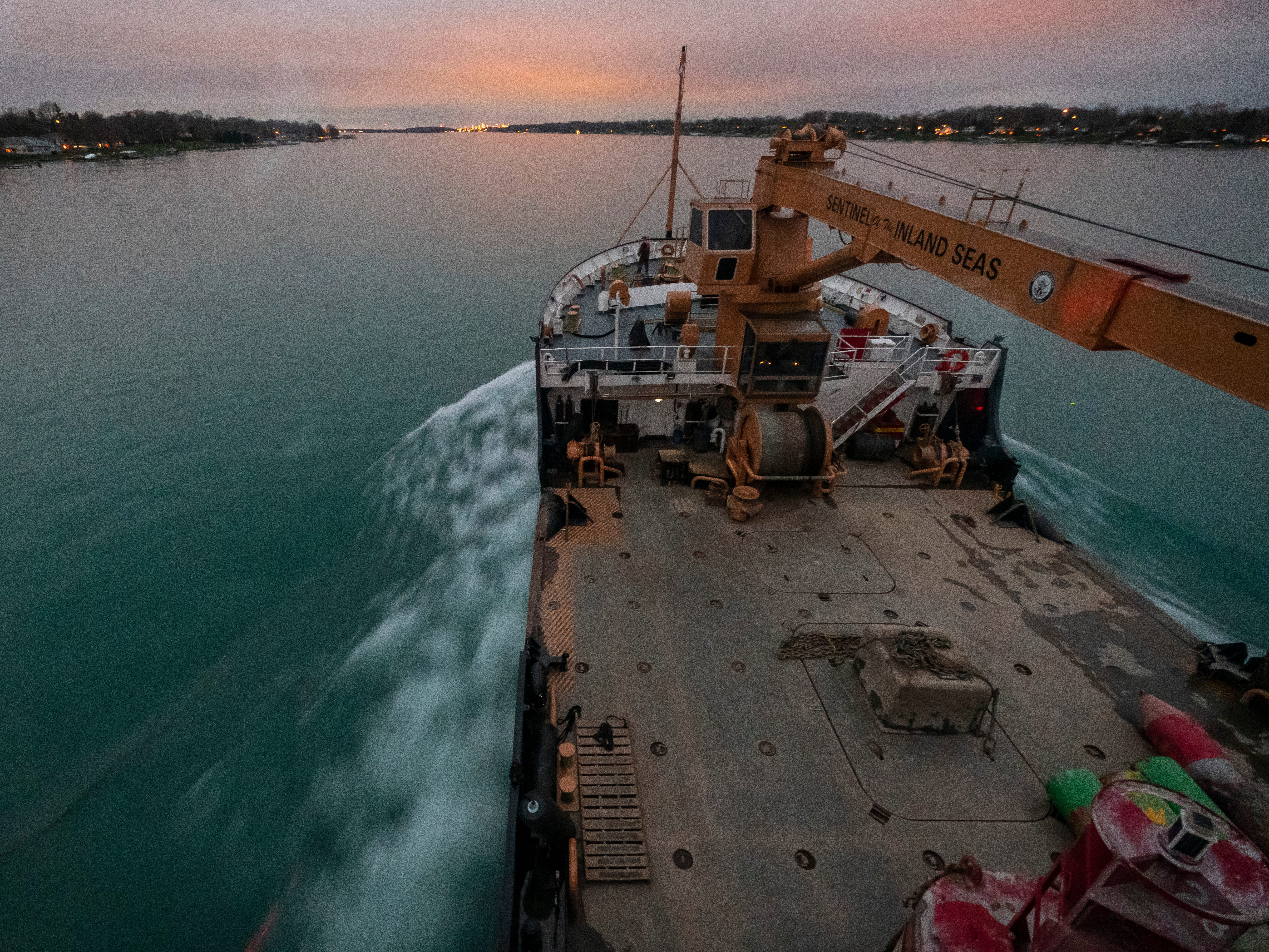 The sun begins to set as the USCGC Hollyhock is upbound on the St. Clair River Thursday, April 25, 2019, towards Blue Water Aggregates in Marysville. The ship will moor there for the night, and in the morning it will be loaded with more buoys before getting underway again.