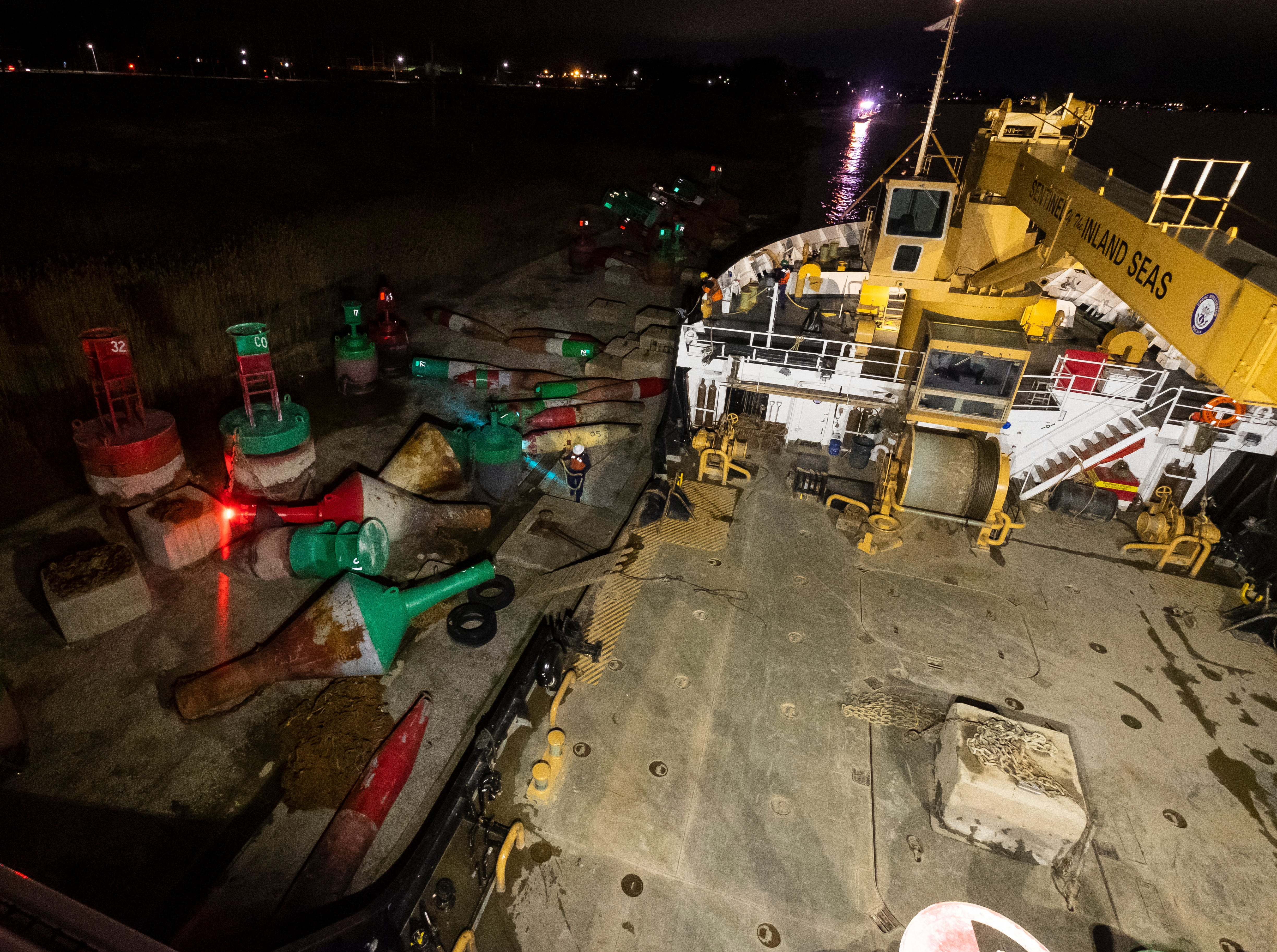 Lights on buoys flash in the darkness at the USCGC Hollyhock's mooring site Thursday, April 25, 2019 at Blue Water Aggregates in Marysville. The buoys will be loaded onto the ship's buoy deck before it gets underway the following morning.