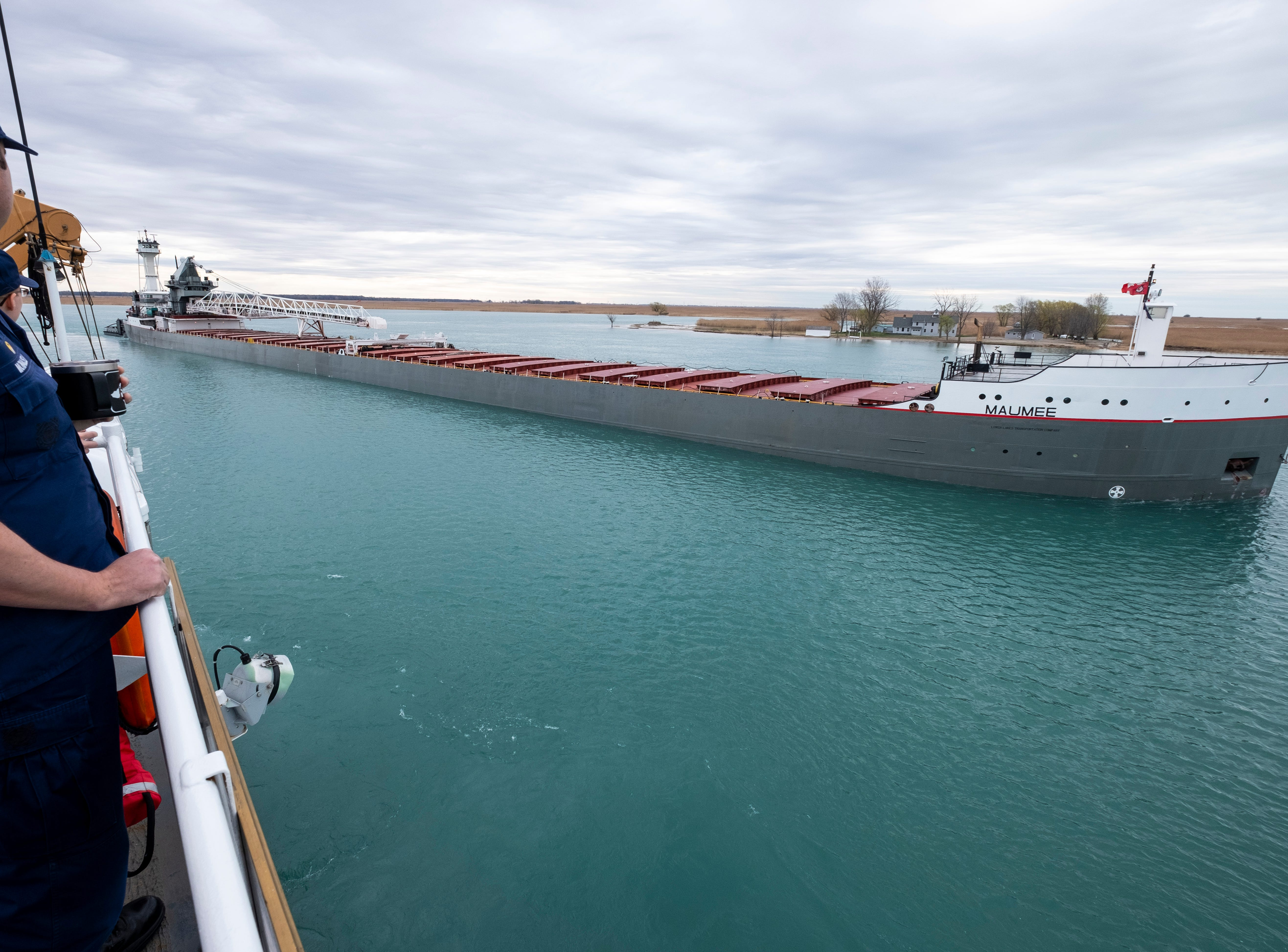 U.S. Coast Guard Lt. Cmdr. Nick Monacelli watches as the Maumee barge, pushed by the tug Victory, passes the USCGC Hollyhock Thursday, April 25, 2019 on the southern end of the St. Clair River.