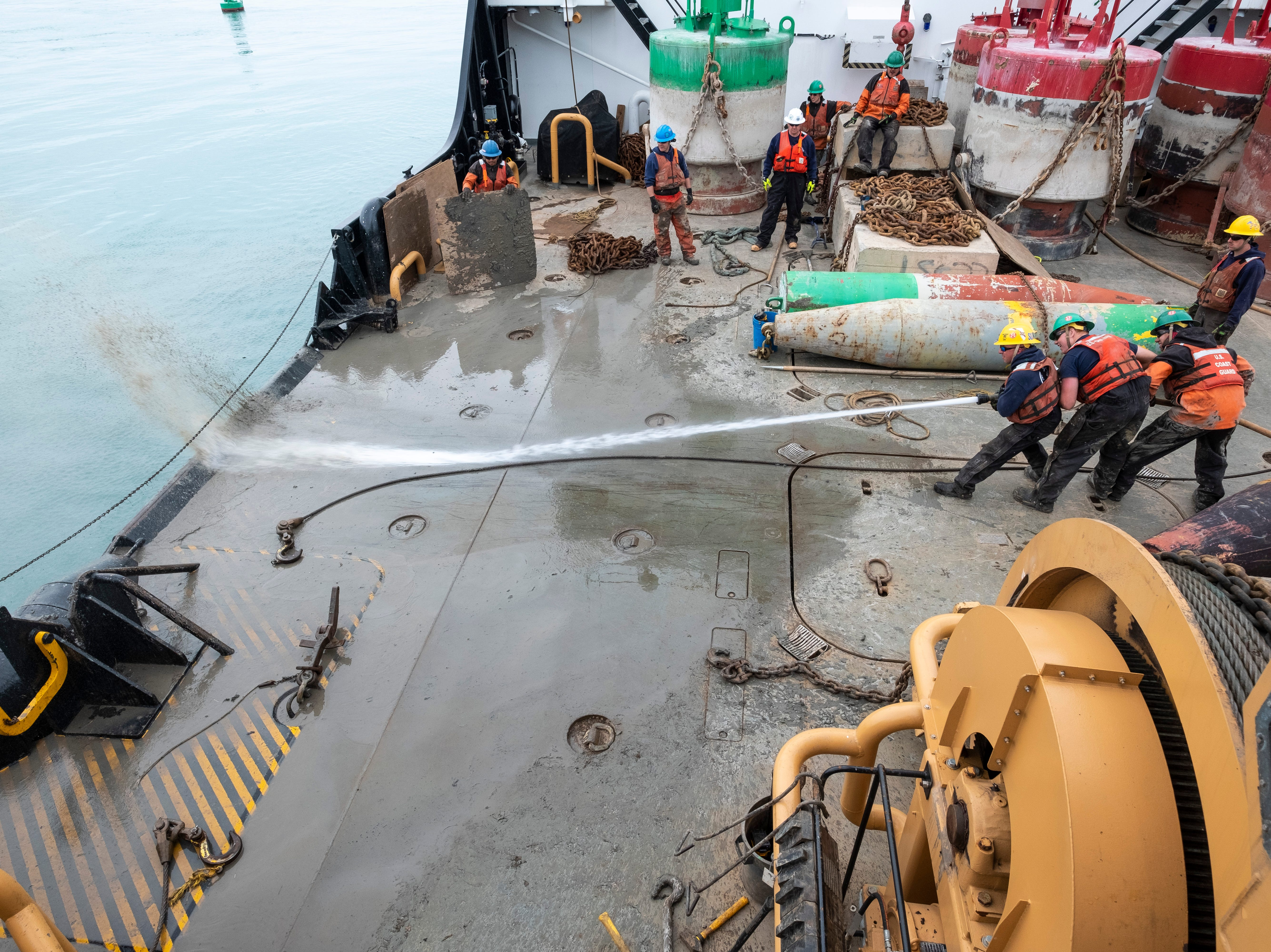 After the slab has been attached to a buoy and set back into the lake, crewmembers use a pressurized hose to clear mud off the buoy deck of the USCGC Hollyhock Thursday, April 25, 2019.