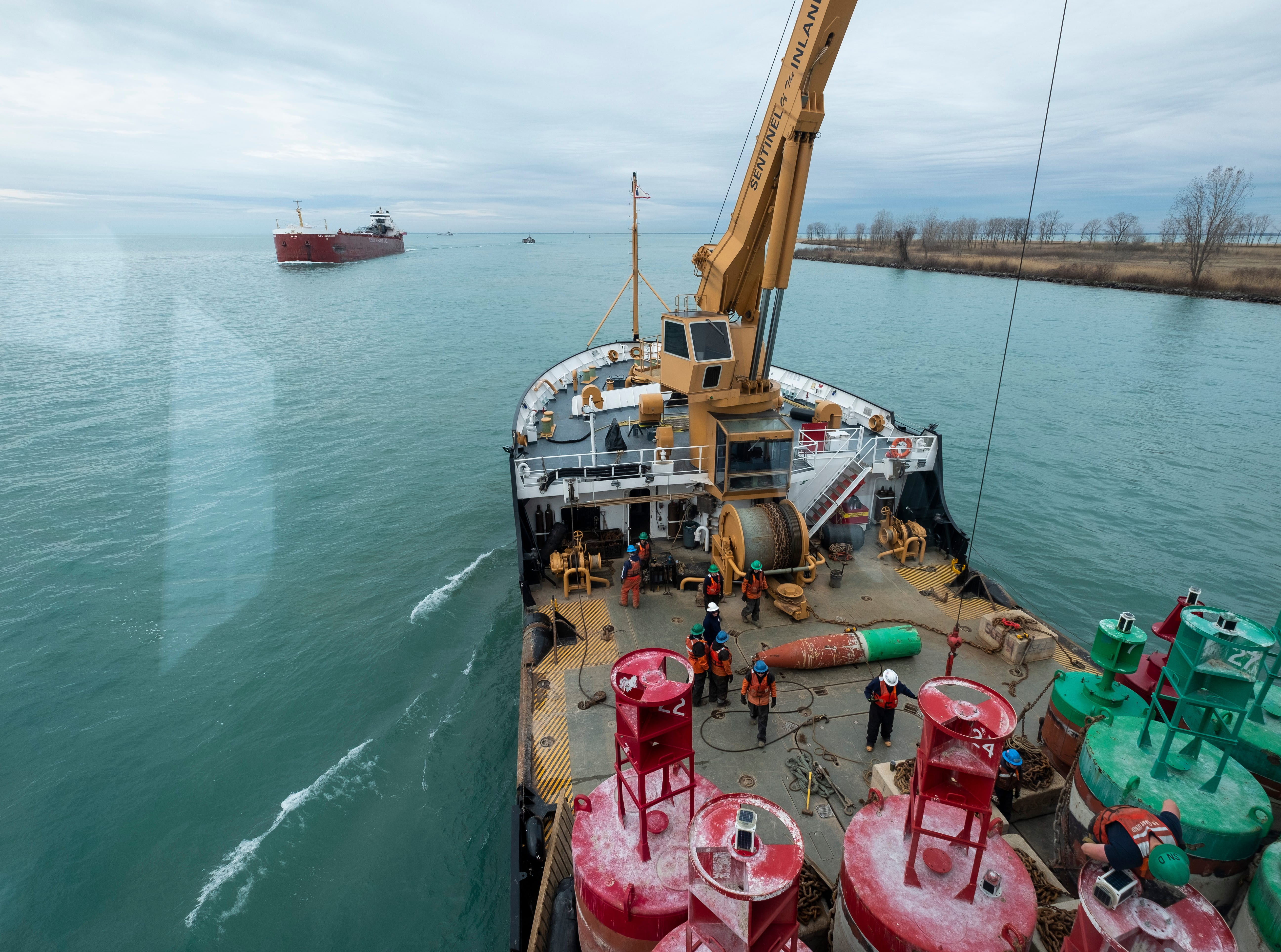 The CSL Assiniboine passes the Hollyhock's port side bow while crews work to attach a crain to a buoy on the cutter's deck Thursday, April 25, 2019 on the St. Clair River.