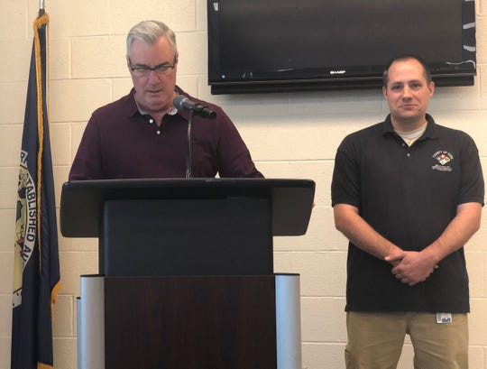 York County Commissioner Chris Reilly announces that Jason Witz (at right) of the York County 911 Center was named administrative support staffer of the year at a ceremony on April 18, 2019.