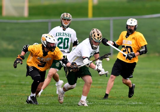 Drew Snelbaker of York Catholic battles for the win on the faceoff as Red Lion's Nic Shultz tries to knock the ball away, Thursday, April 25, 2019.