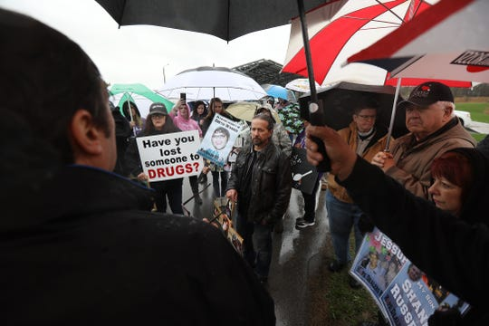 Family's of loved ones hold photos and protest RDC, Rochester Drug Cooperative, from across the street.  The rally was in response to the recent federal charges against RDC.  Mark Assini, former Gates Town Supervisor, talks to the crowd at the start of the rally.