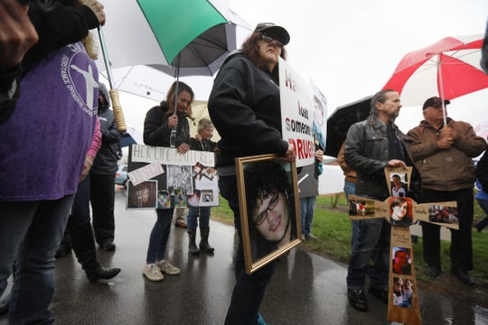 Families of loved ones hold photos and protest in 2019 across from RDC, Rochester Drug Cooperative. The rally was in response to the federal charges against RDC. Catherine Warren of Webster holding photos of her 22-year-old son, Curtis James Warren, who died from drugs, and Dean Lucas of Webster, holding a cross with photos of his son, Lee Lucas, join other families who lost loved ones due to drug abuse listen to a speech before lining up for a silent protest.