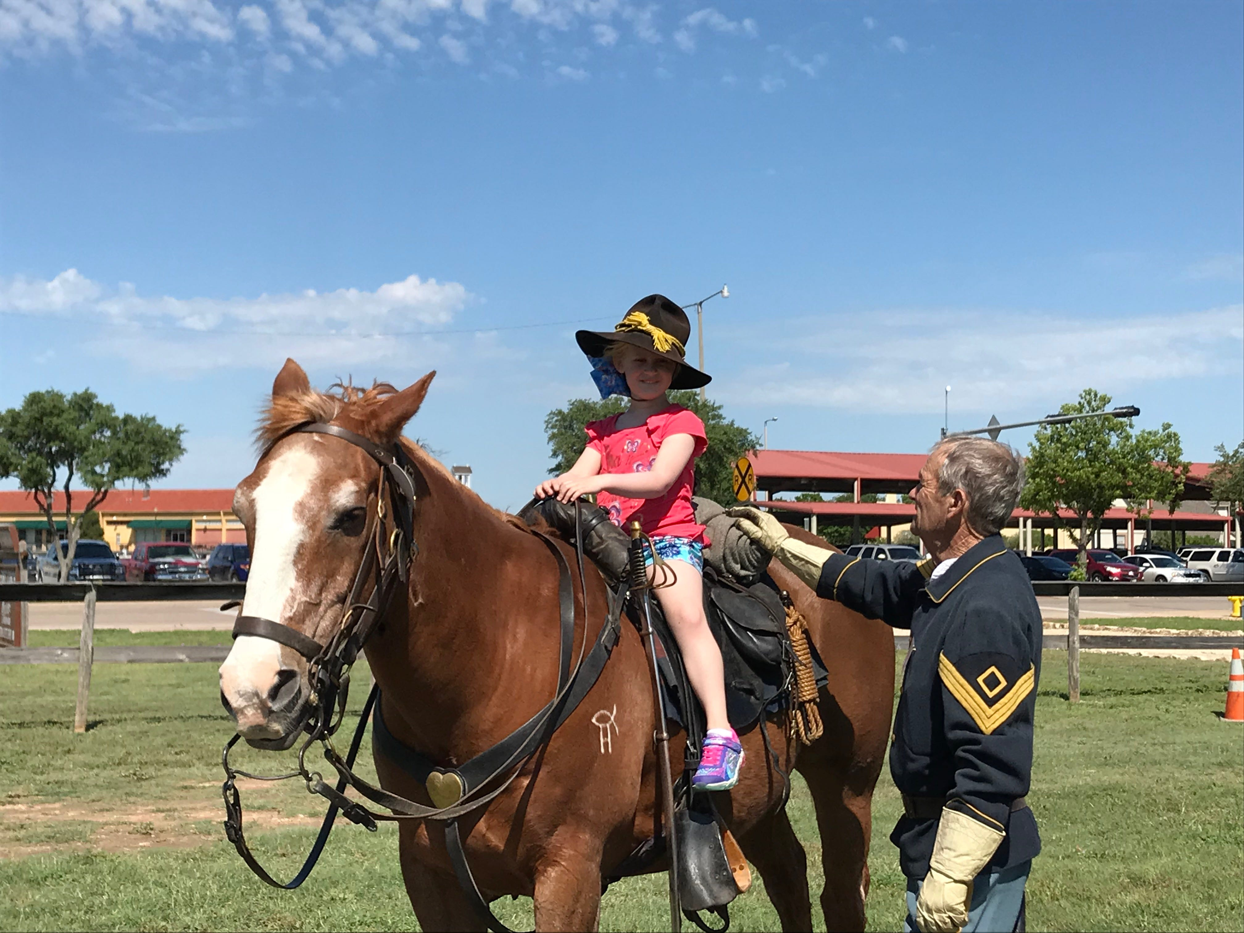 Emma Carr, 6, smiles at Sgt. Ron Perry, from Ft. Concho's Company D, at the Regional Cavalry Competition at Fort Concho, 630 S. Oakes St. on Friday, April 26, 2019.