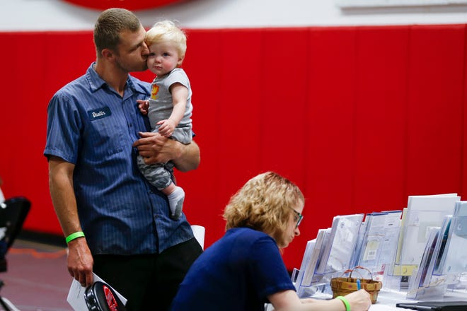 Dustin Knight holds his 9-month-old son Christian as his wife, Kendra, fills out paperwork during an event for 417 Rentals tenants to get help at the Springfield Dream Center on Friday, April 26, 2019.