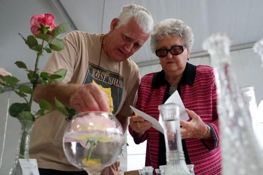 Bob Maxwell, left, and Montine Herring work together to put together Maxwell's roses for display. Professional and novice rose growers prep their most beautiful blooms to show off at the Thomasville Rose Show and Festival Friday, April 26, 2019.