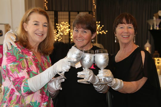 """Suzi James, left, Wendy Dwyer and Robyn Hutchinson with their """"Shine Your Light"""" glasses at the Mustard Seed MinistriesTea and Fashion Show."""