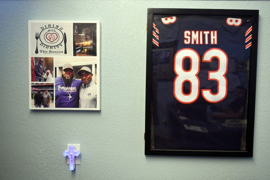 Photos and an NFL jersey that was once worn by former Vero Beach High School football star Eric Smith hang in the main office at The Source, a Christian ministry serving the poor and homeless in Vero Beach. Smith, now works there full-time sharing his story with others.
