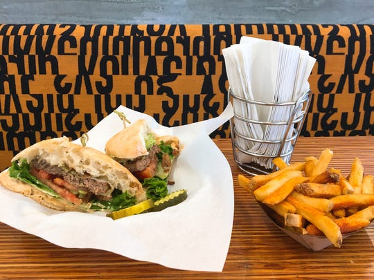 """A """"beef fun chipotle"""" burger on ciabatta, left, is seen with an order of Cajun fries at Fun Burger in Simi Valley."""