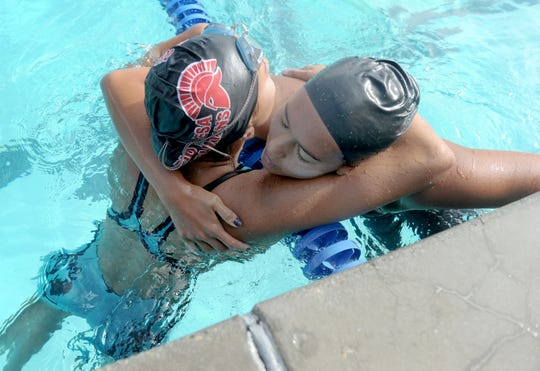 Rio Mesa's Teagan Monroe, left, hugs good friend Tea Laughlin of Ventura after the two competed against each other in the girls 100 backstroke at the Pacific View League Swimming Championships on Thursday at Buena High. Laughlin was first and Monroe was second.